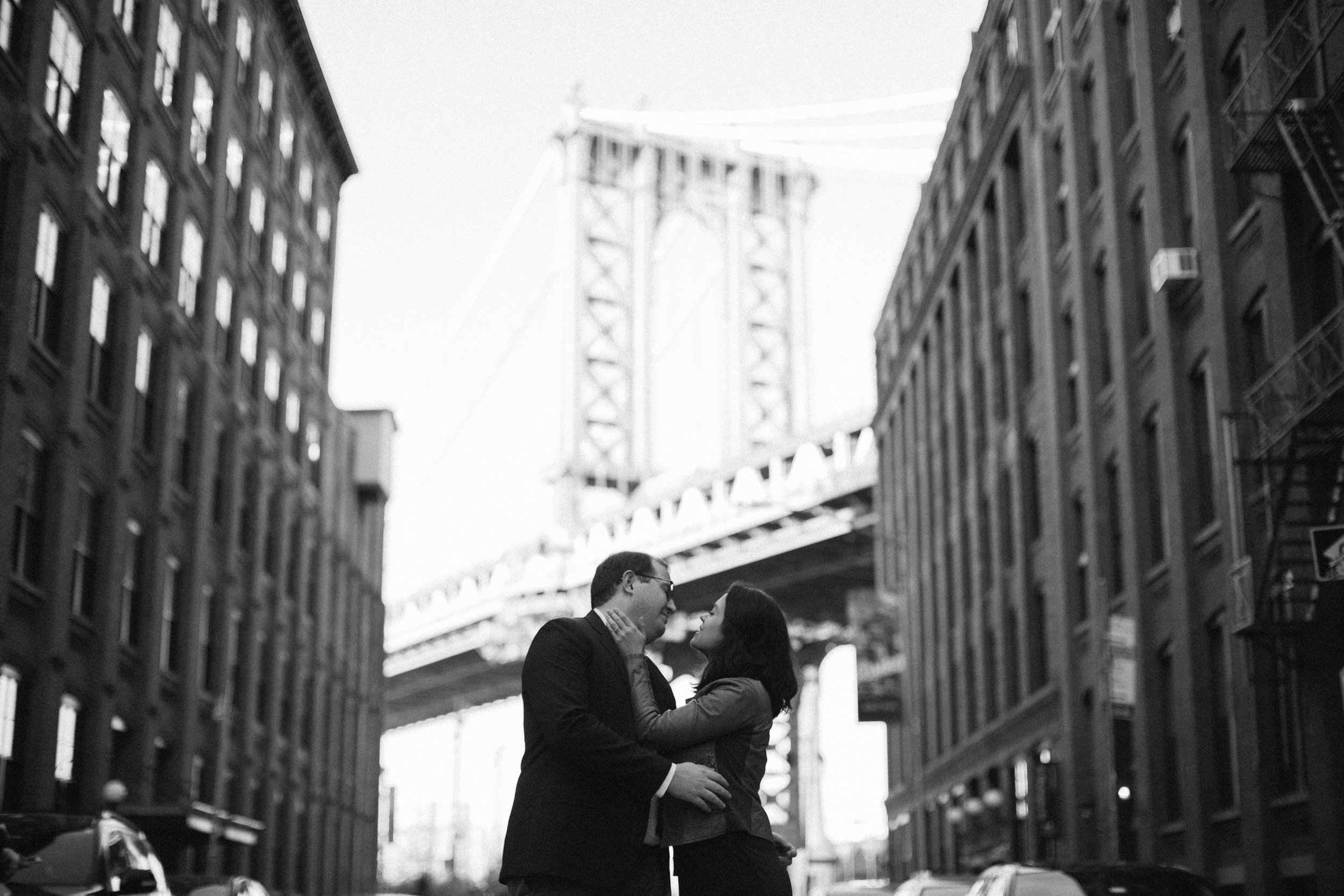 couple kissing in dumbo with a view of the brooklyn bridge
