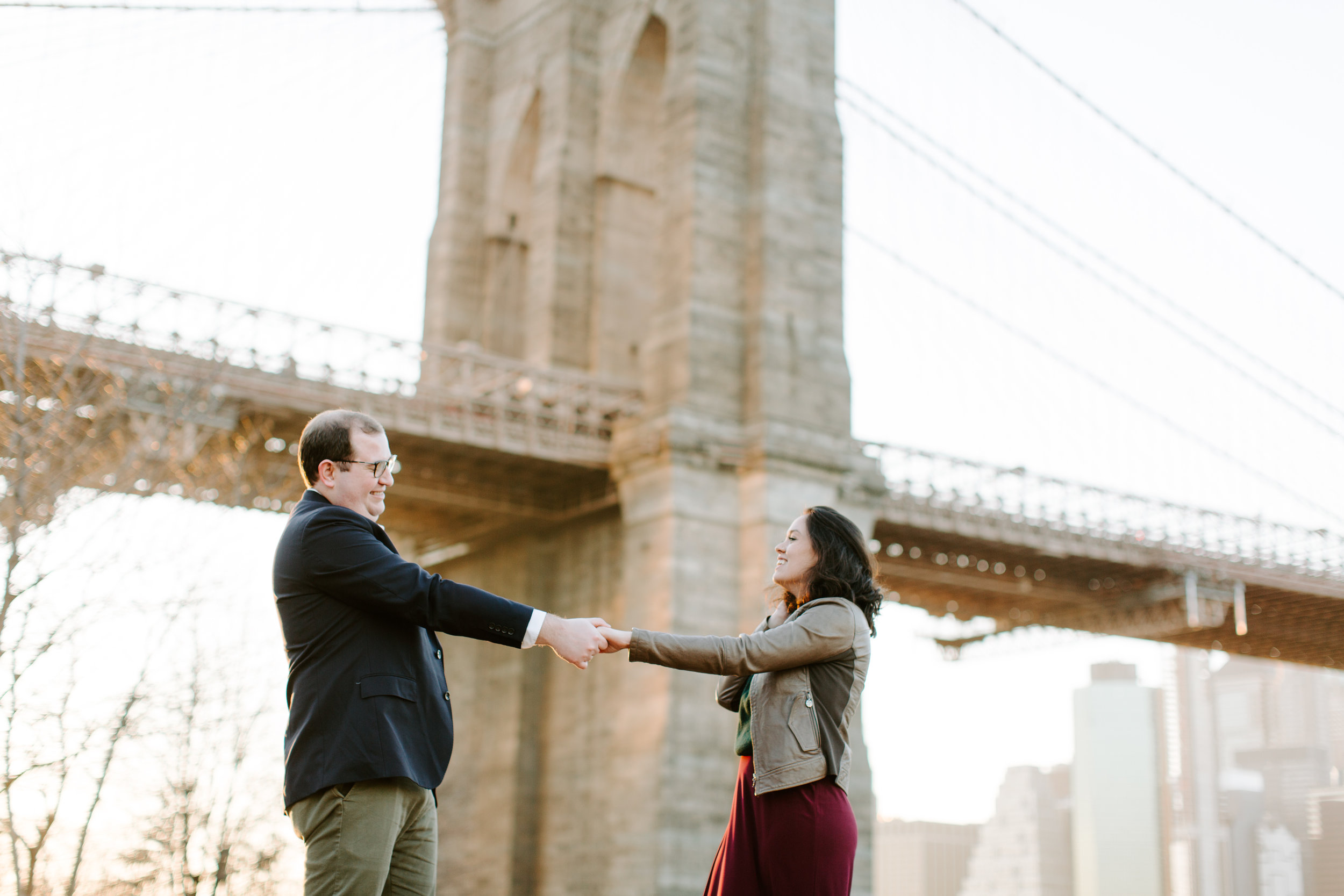 couple holding hands in dumbo by the brooklyn bridge