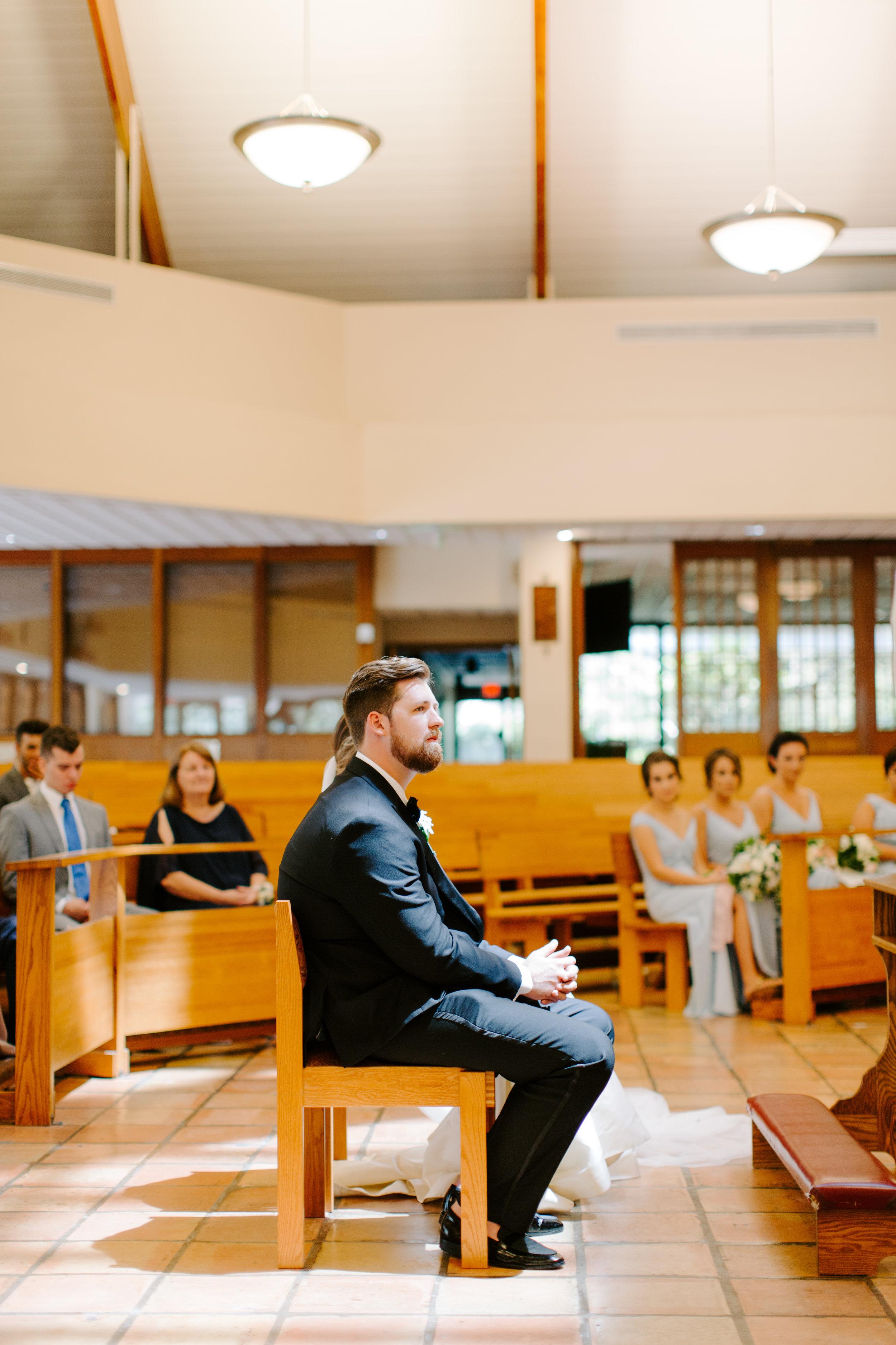 groom sitting in catholic ceremony