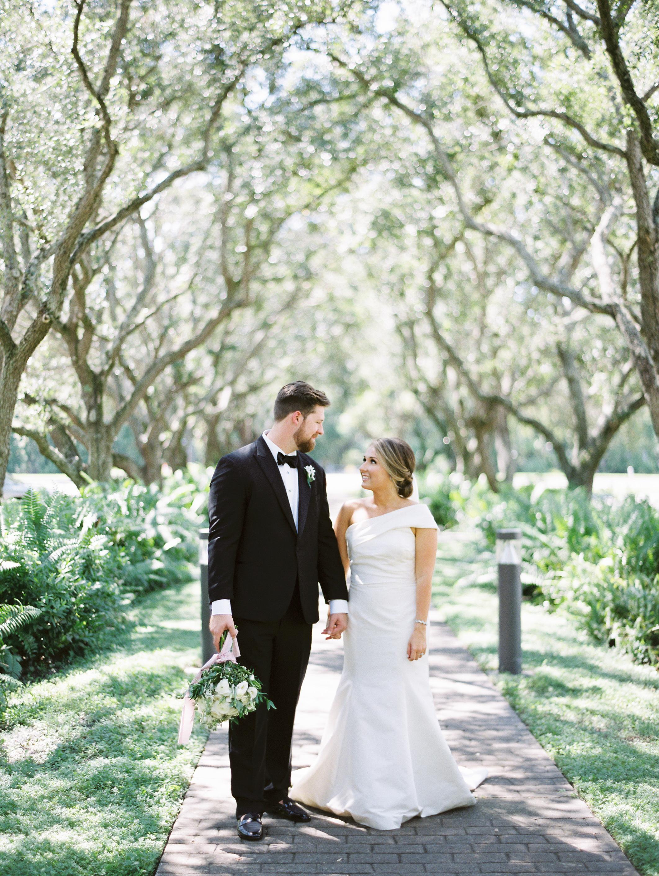 bride and groom walking through trees on film