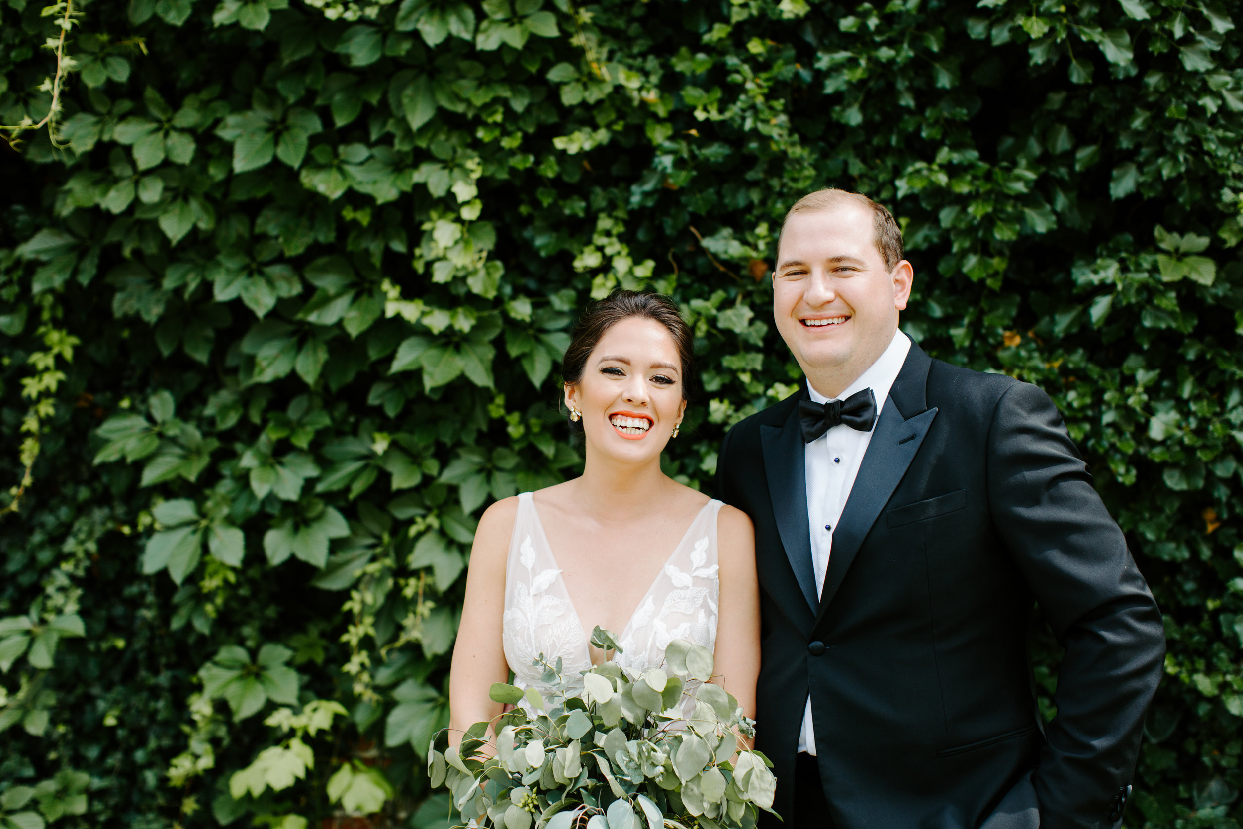 greenery wall at the ravington with bride and groom