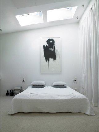 The bedroom is simple and embraces the daylight.