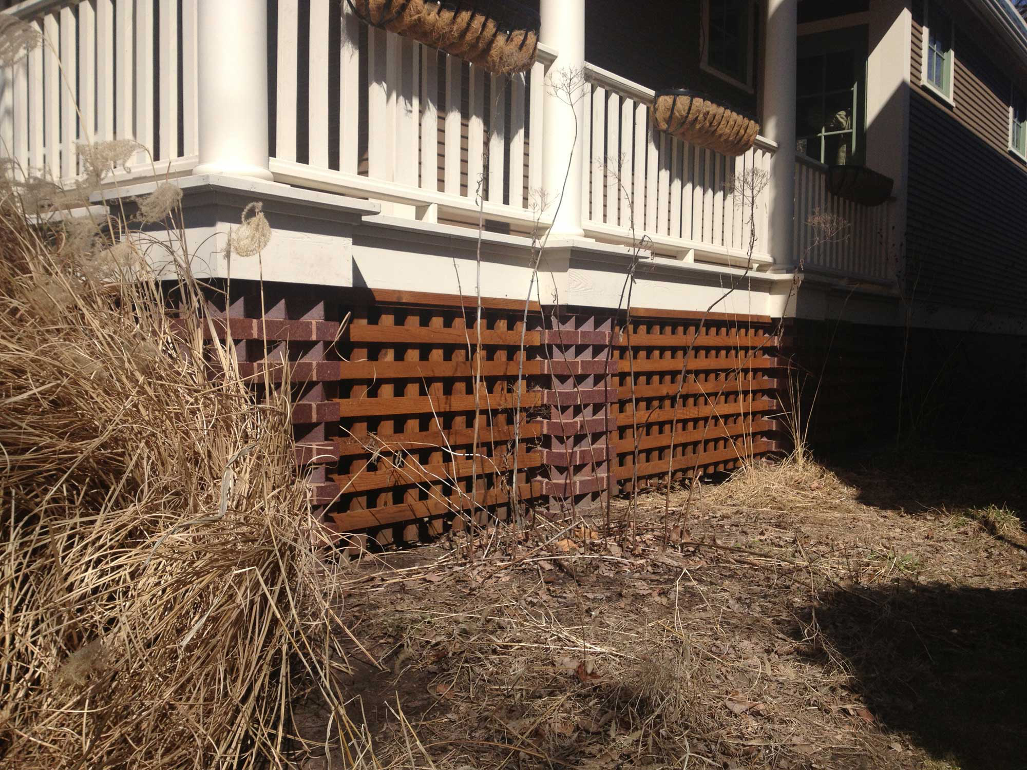 The cedar trellis is aligned with the masonry. Note the native prairie grass lawn.