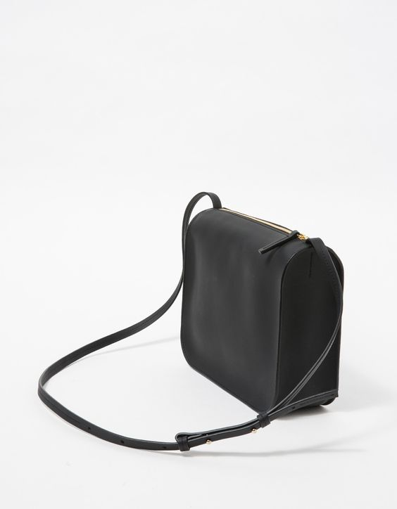 CUERO&MOR Crossbody Bag  From Cuero&Mør, a minimalist smooth leather crossbady in Black. Features top zipper, leather pull tab, gold hardware, adjustable shoulder strap, unlined, standing structure and front gold pressed logo.