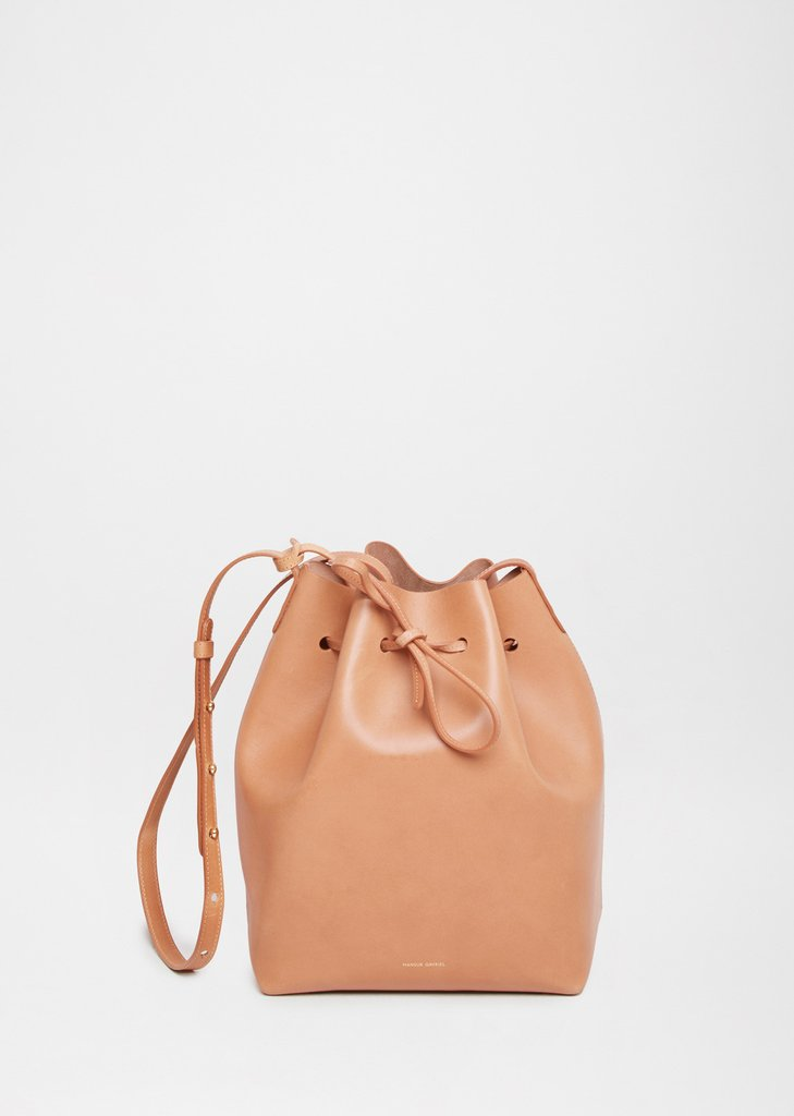MANSUR GAVRIEL Bucket Bag  The signature bucket bag from Mansur Gavriel with cinch top closure and contrast, resin coated interior. A versatile, simple silhouette with minimal hardware and stitching, made with structured vegetable tanned leather that develops a beautiful, personal patina with use.