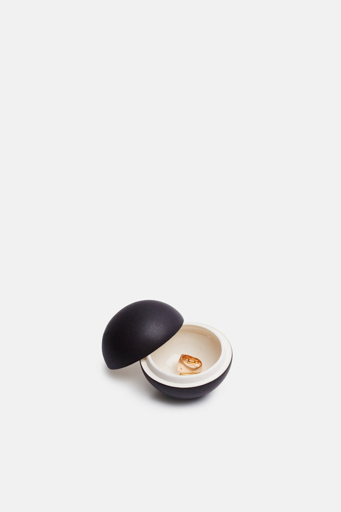 JULIE BONDE Matte Black Mini Spherical Lidded Container  Handmade bonbonnière is both functional and decorative: a bisected sphere of black porcelain that opens to reveal a glossy, cream-hued cache for treasures or treats.