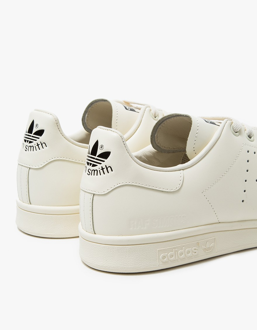 ADIDAS x RAF SIMONS Raf Simons Stan Smith in Cream/Black  Modern Stan Smith from Adidas in collaboration with Raf Simons. Cream with Black detailing. Lace-up front with flat cotton laces. Padded collar. Perforated 'R' side panel detailing. Raf Simons tongue logo. Embossed 'Trefoil' heel logo. Embossed Raf Simons outer heel branding.