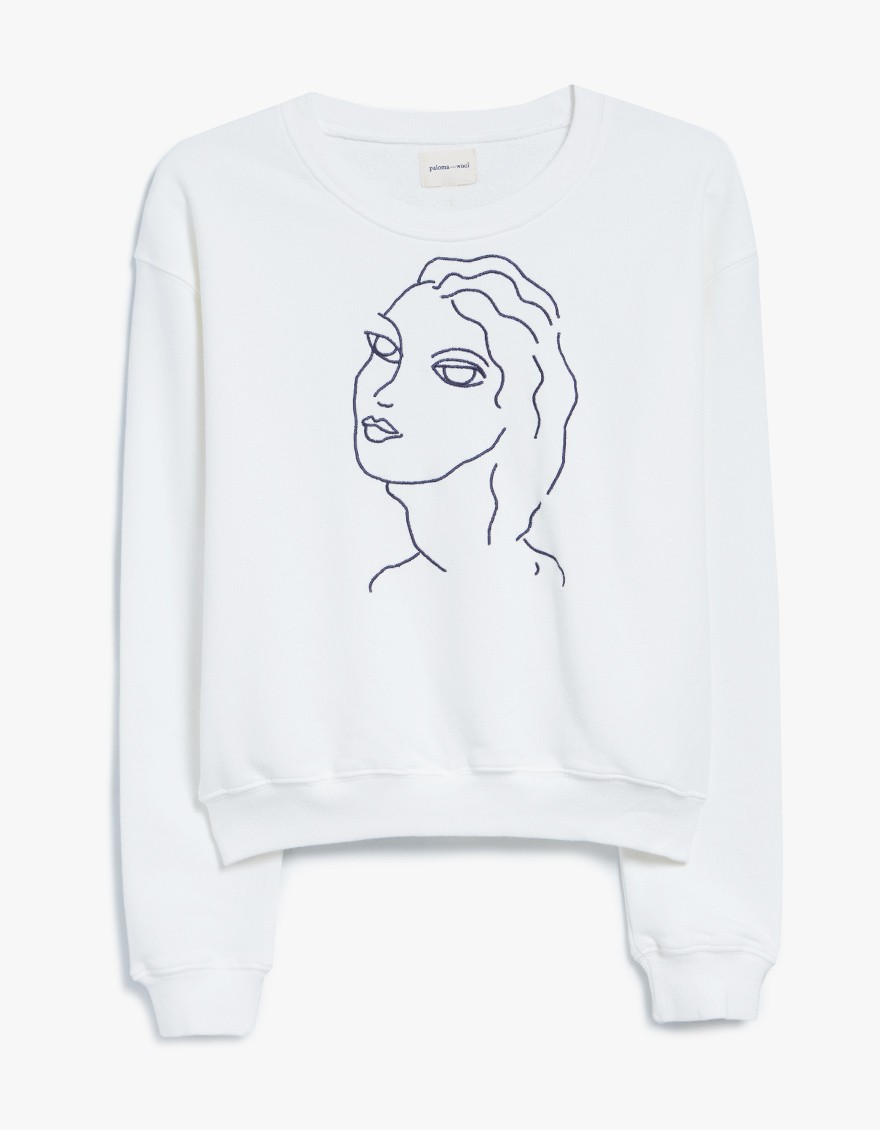PALOMA WOOL Guiri Sweatshirt  Pullover sweatshirt from Paloma Wool in White. Crew neckline. Dropped shoulders. Long sleeves. Embroidered female figure at front drawn by Tana Latorre. Ribbed neck, cuffs and hem. Slightly cropped. Boxy silhouette.