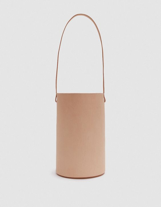 BUILDING BLOCK Basket in Nude  Unlined cylindrical leather shoulder bag from Building Block in Nude. Main compartment with magnetic closure. Shoulder strap. Detachable coin purse with zip closure. Tonal stitching. Structured base with embossed logo.