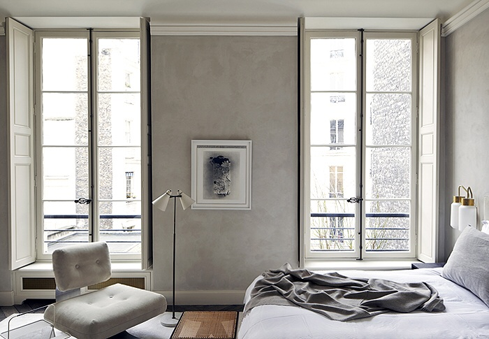 Layered grey's within a bedroom with tall open windows