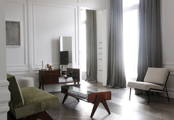 Long stunning drapes pooling on the parquetry floor with bold angular furniture.