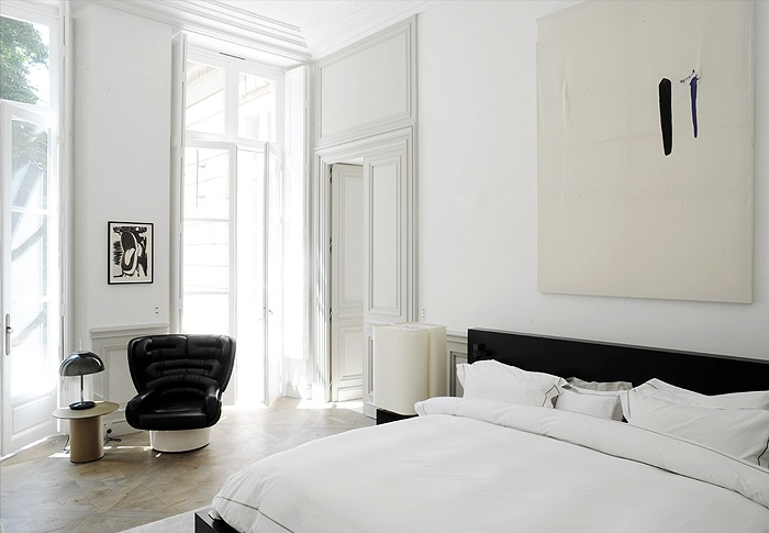 White bedroom with floor to ceiling doors with subtle contrasting furniture and art.