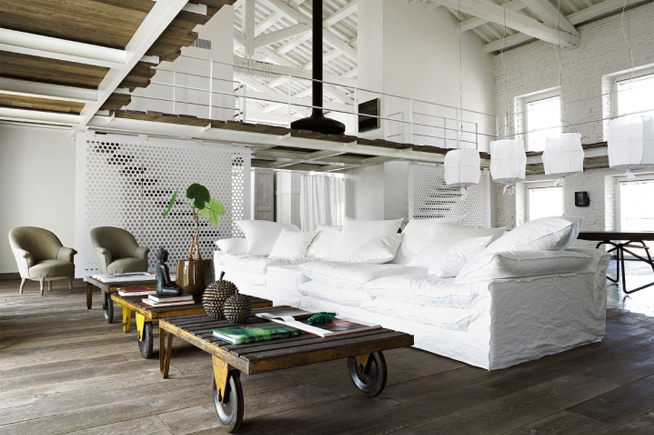 white linen sofa with industrial coffee table with oversized wheels, white wash walls and ceilings.