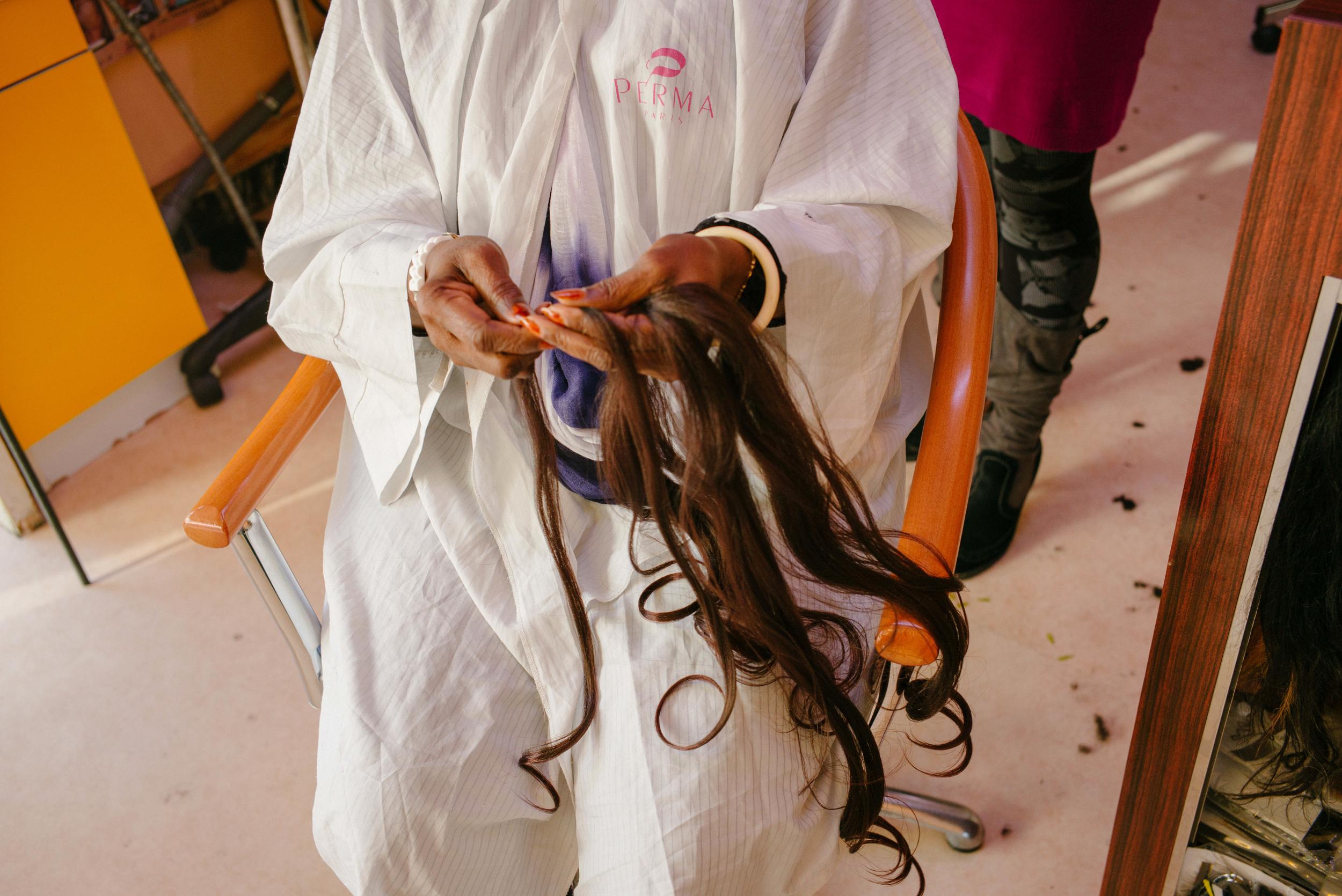 Thérèse, originaire du Bénin, tient dans ses mains les extensions, des cheveux qu'elle distribue à Missoule.