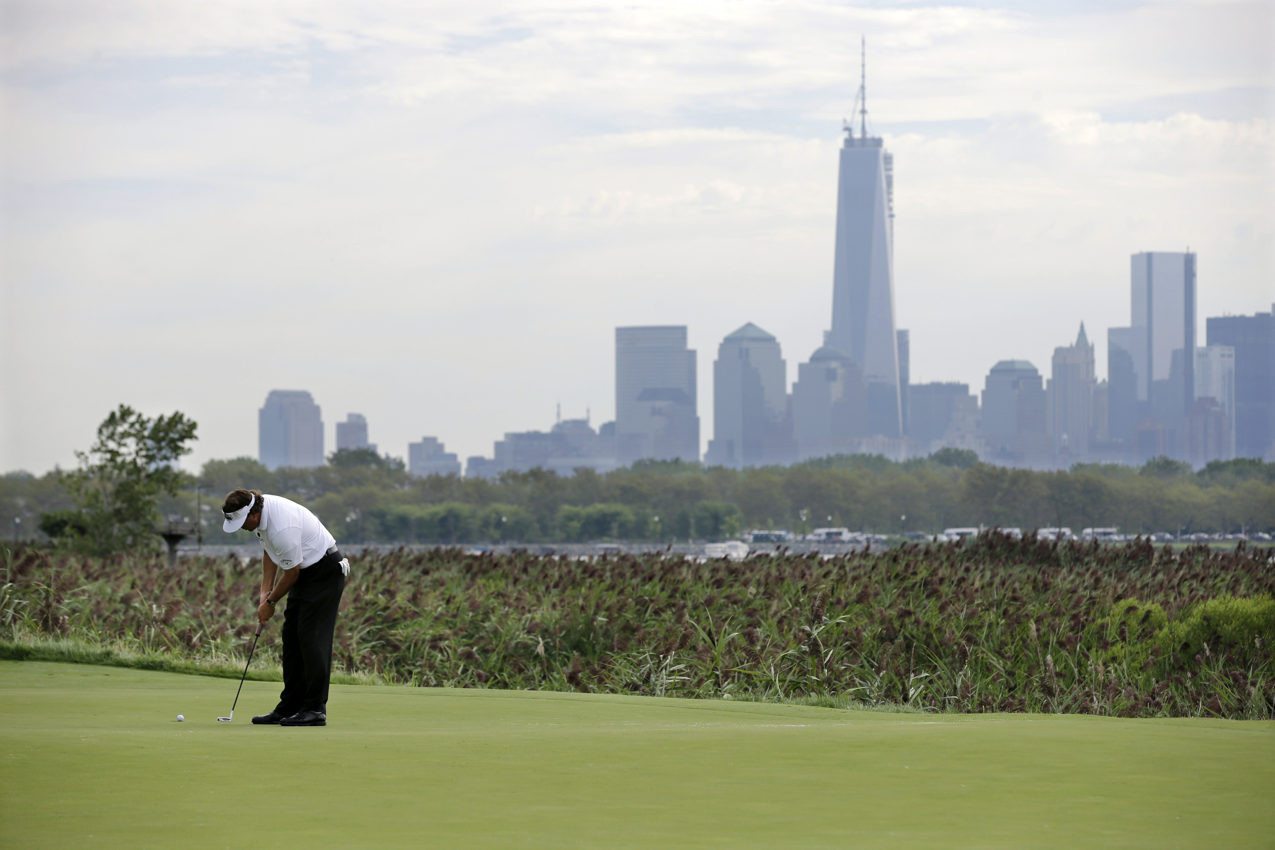 Phil Mickelson watches a putt as One World Trade Center dominates the epic views from Liberty National. (Photo courtesy of golfweek.com)