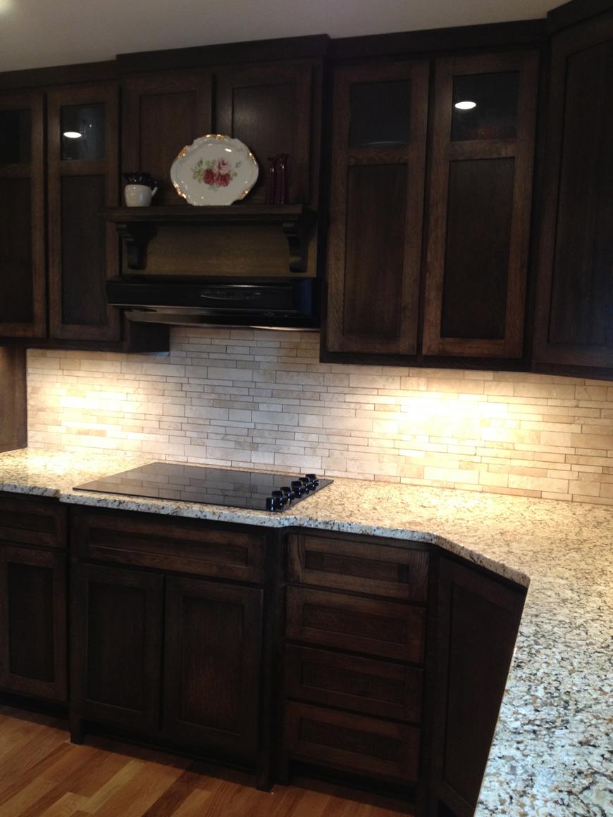 Quartersawn oak cabinets with granite countertops and natural stone backsplash.