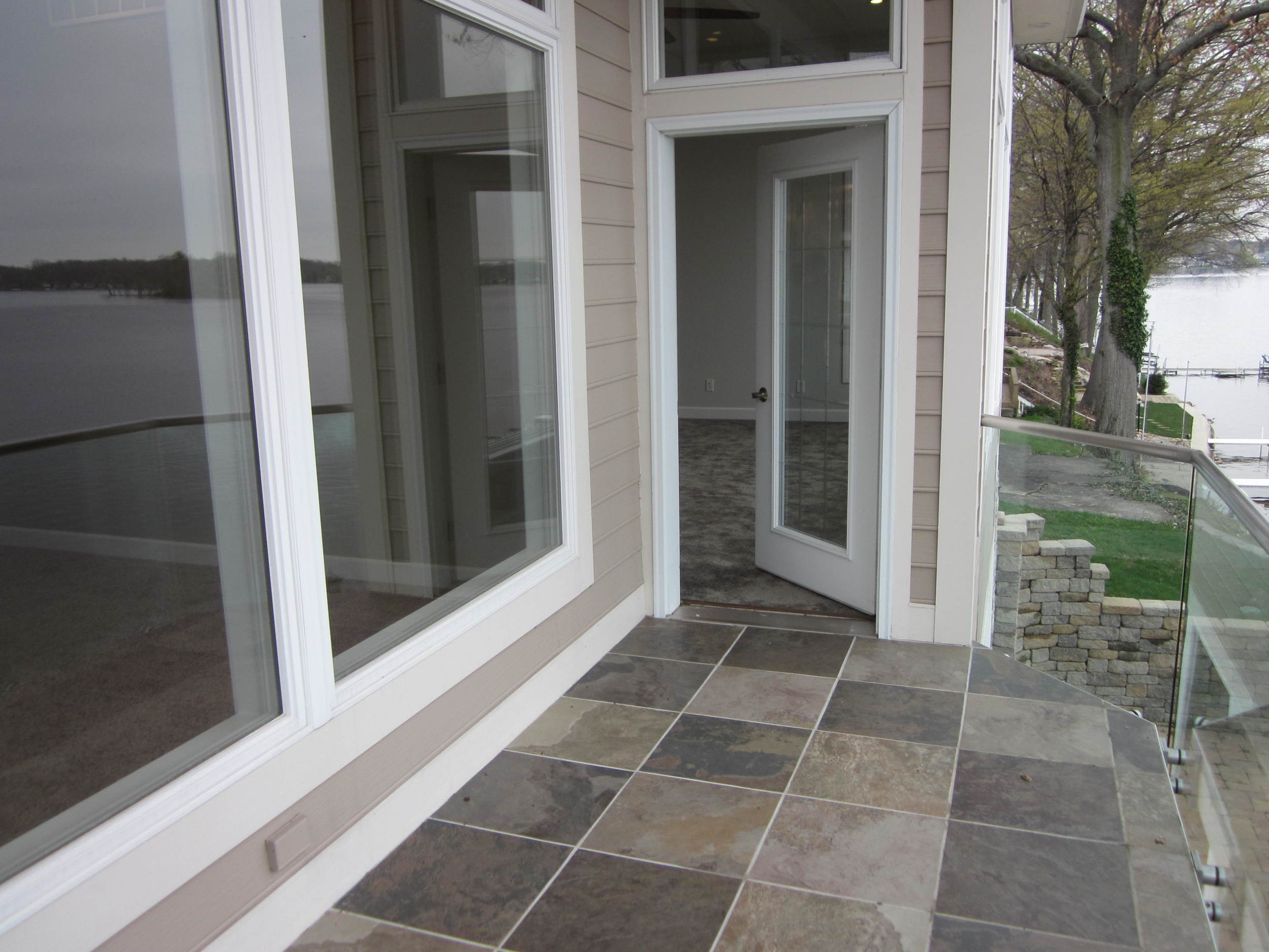 Tiled balcony area with glass railing.