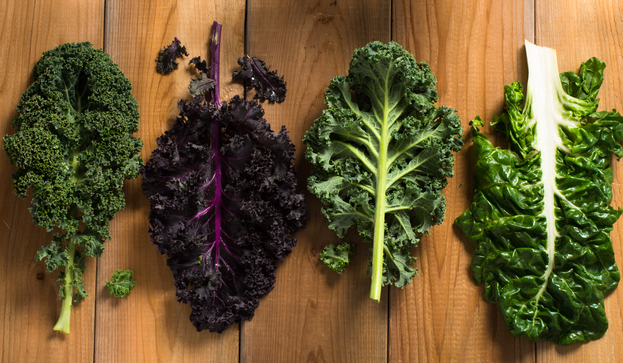 Kale and collard greens on wood surface