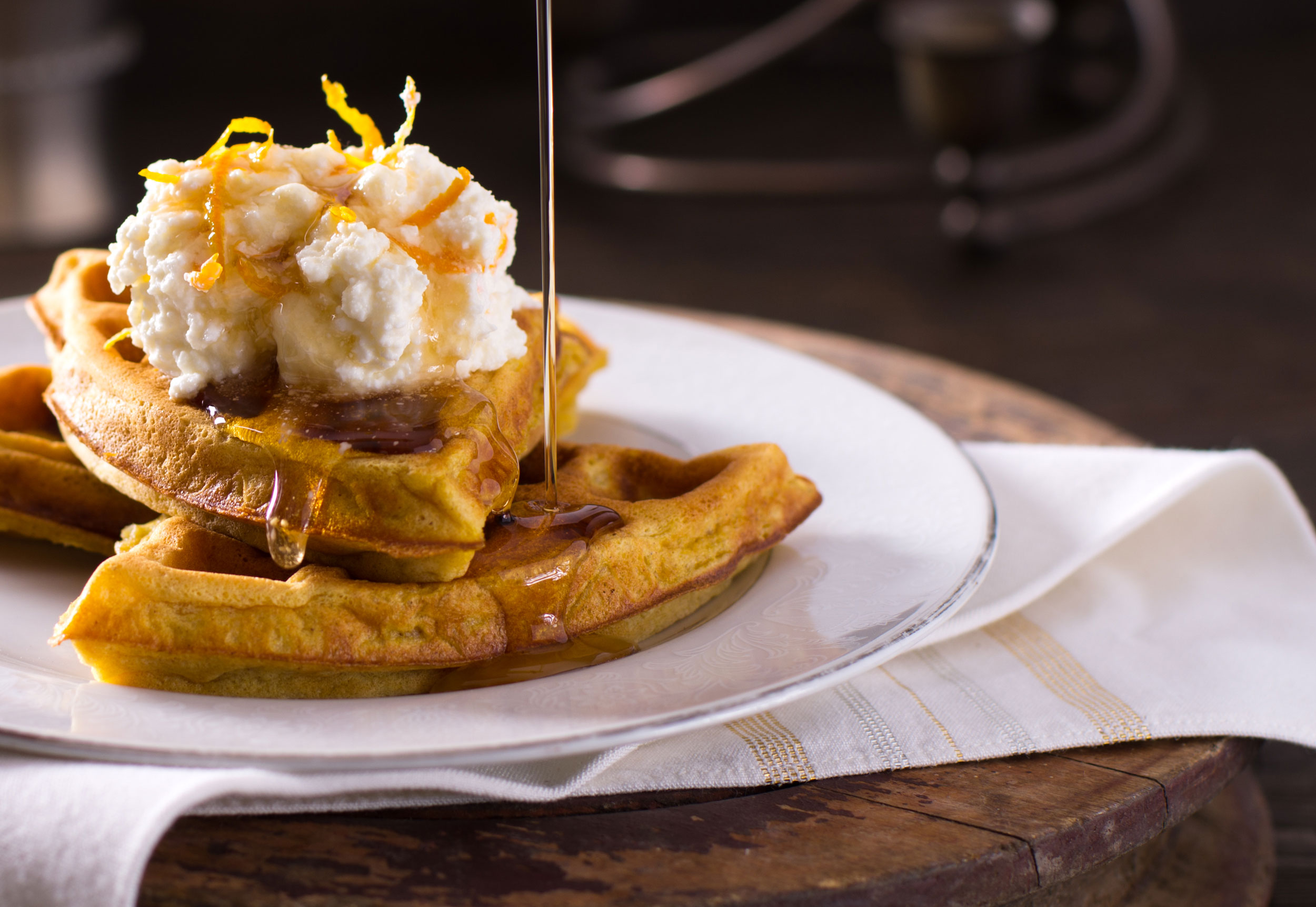 Pumpkin waffles with orange ricotta cheese and maple syrup pour