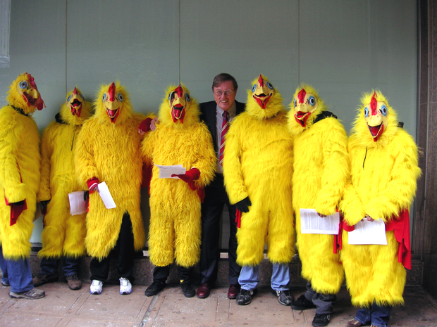 "Steve Andrews, co-founder of ASPO-USA, poses with kids who were hired by someone in the oil industry to stand outside the ASPO 2009 conference in chicken suits and hand out anti-peak oil propaganda calling the attendees ""Chicken Littles."" (source:  Chris Nelder )"