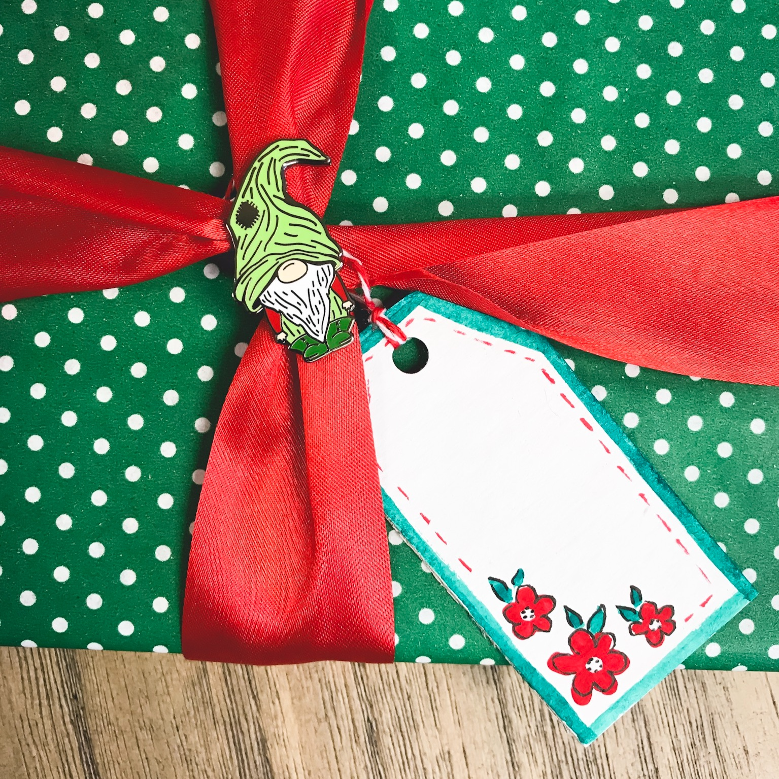 Once your tags are dry, add the ribbon and then tie the to a wrapped gift.   You can find the gnome enamel pin I've used to pin the ribbon in my Etsy shop.