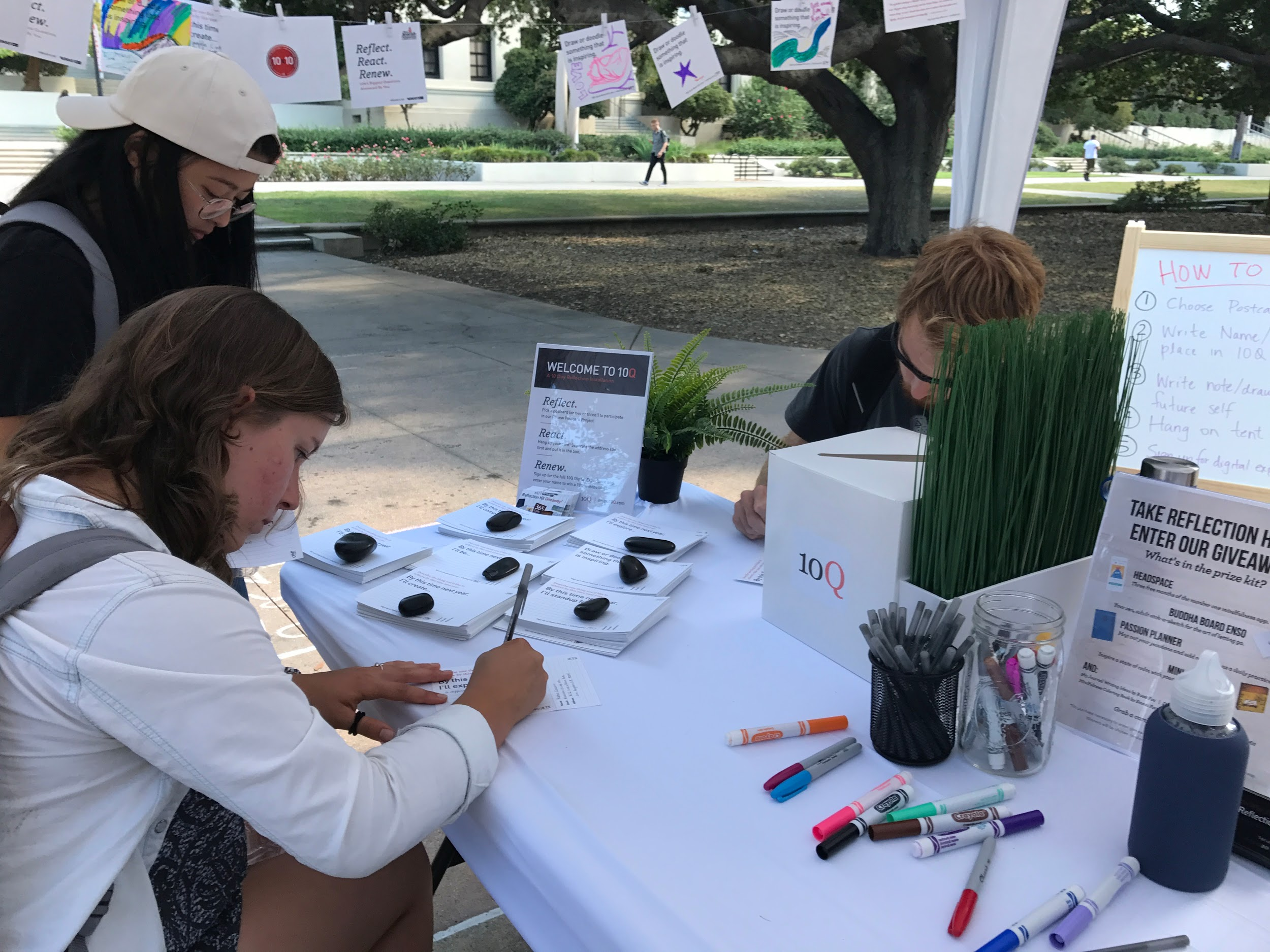 Students write personal reflections on postcards at a 10Q pop-up in Los Angeles.