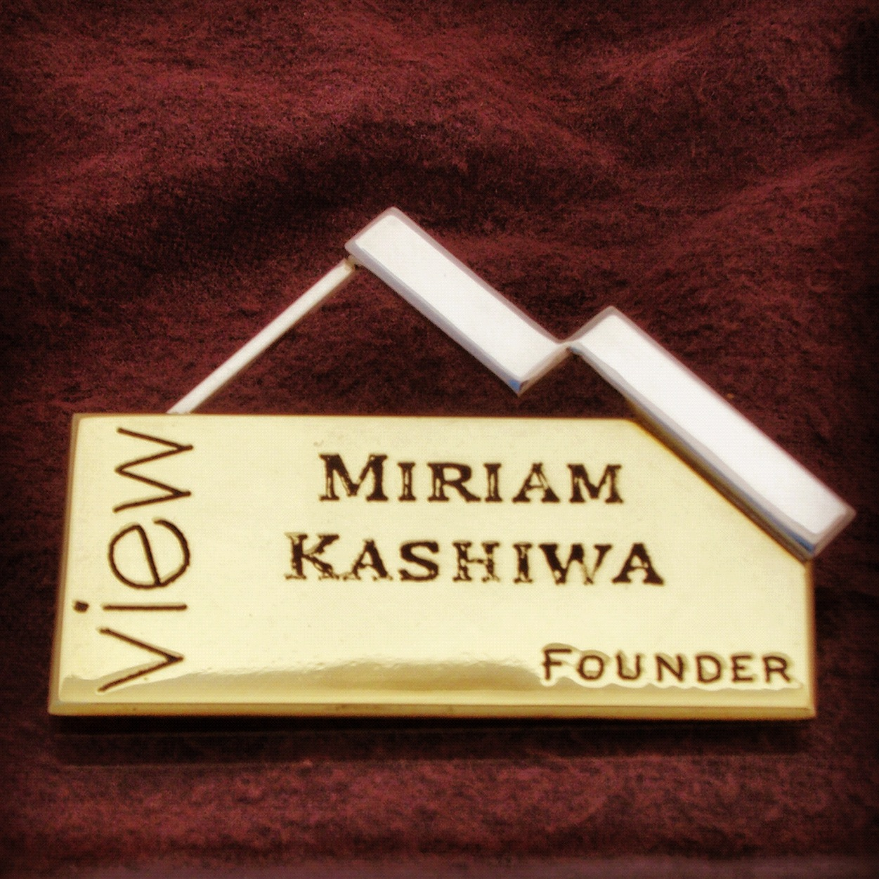 A passing of the torch as worn on the chest of the founder.      A regal  View  nameplate in brass, not only noting Mirnie as the organization's founder, but also reflecting its origins in a polished silver version of the standard that has flown over it for the last few decades.