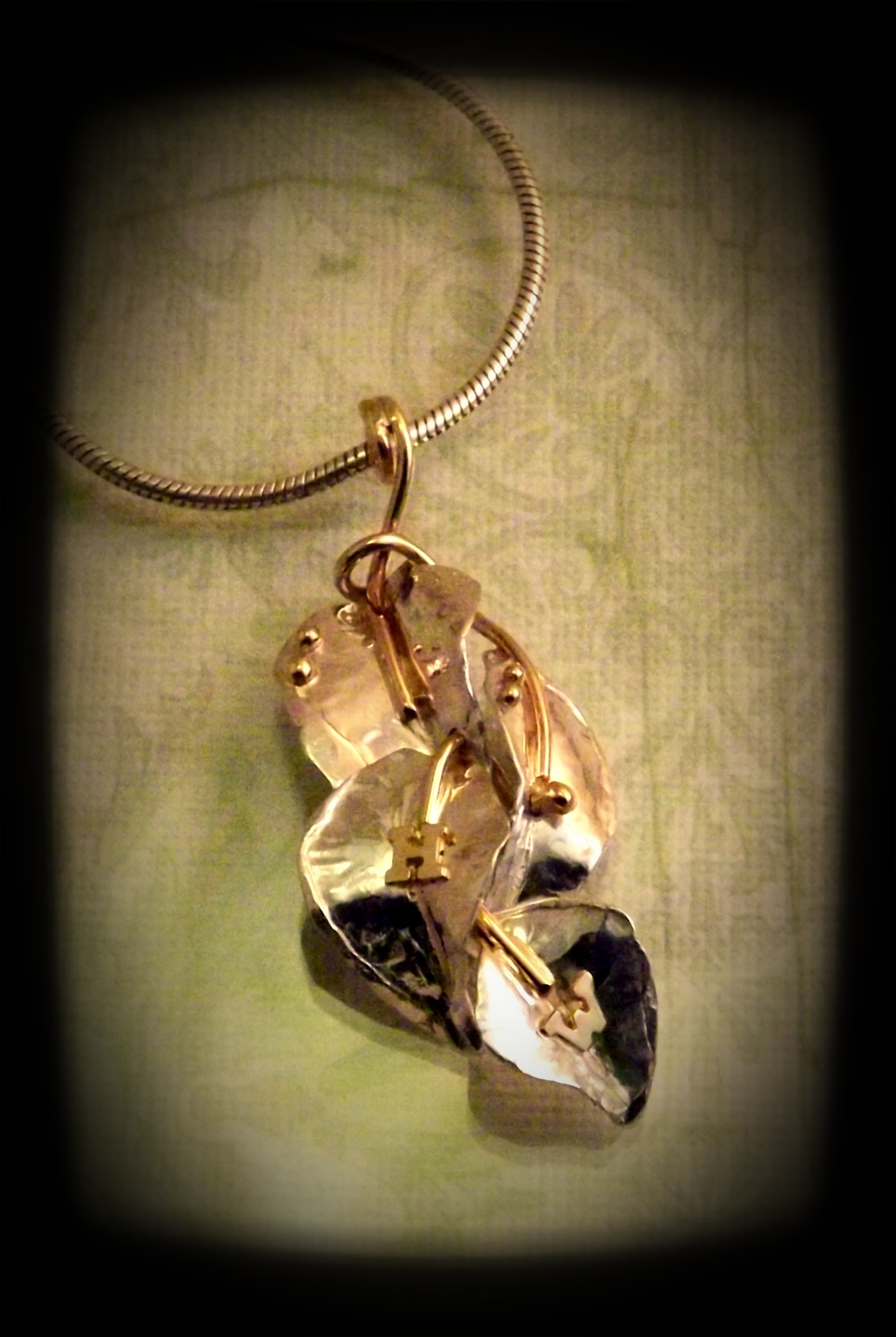 A family pendant with a twist.  Done in silver, the leaves have gold highlights which include the initials of each child.