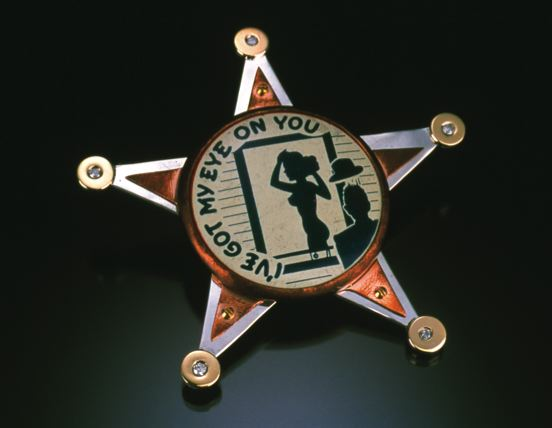 This brooch is a humorously critical view of the overreaching Patriot Act.     14 karat gold discs with flush set diamonds are soldered to a sterling silver base, while a tarnished copper bezel secured with brass hardware holds the punchline in the form of an antique pinback.