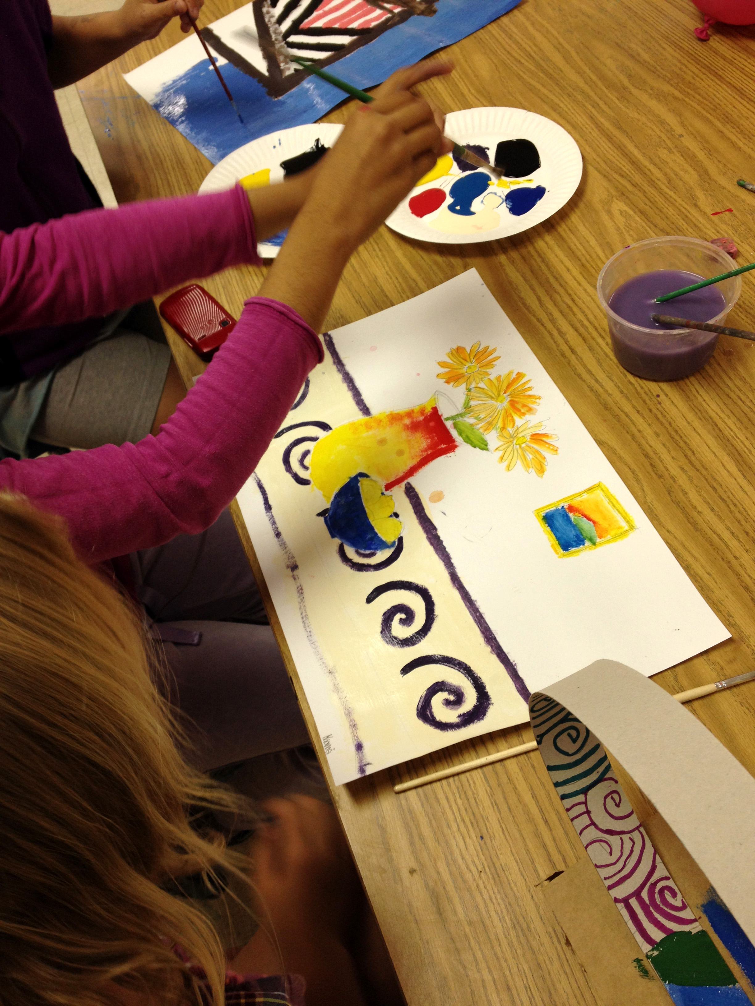 These girls are hard at work creating patterns and painting flowers.