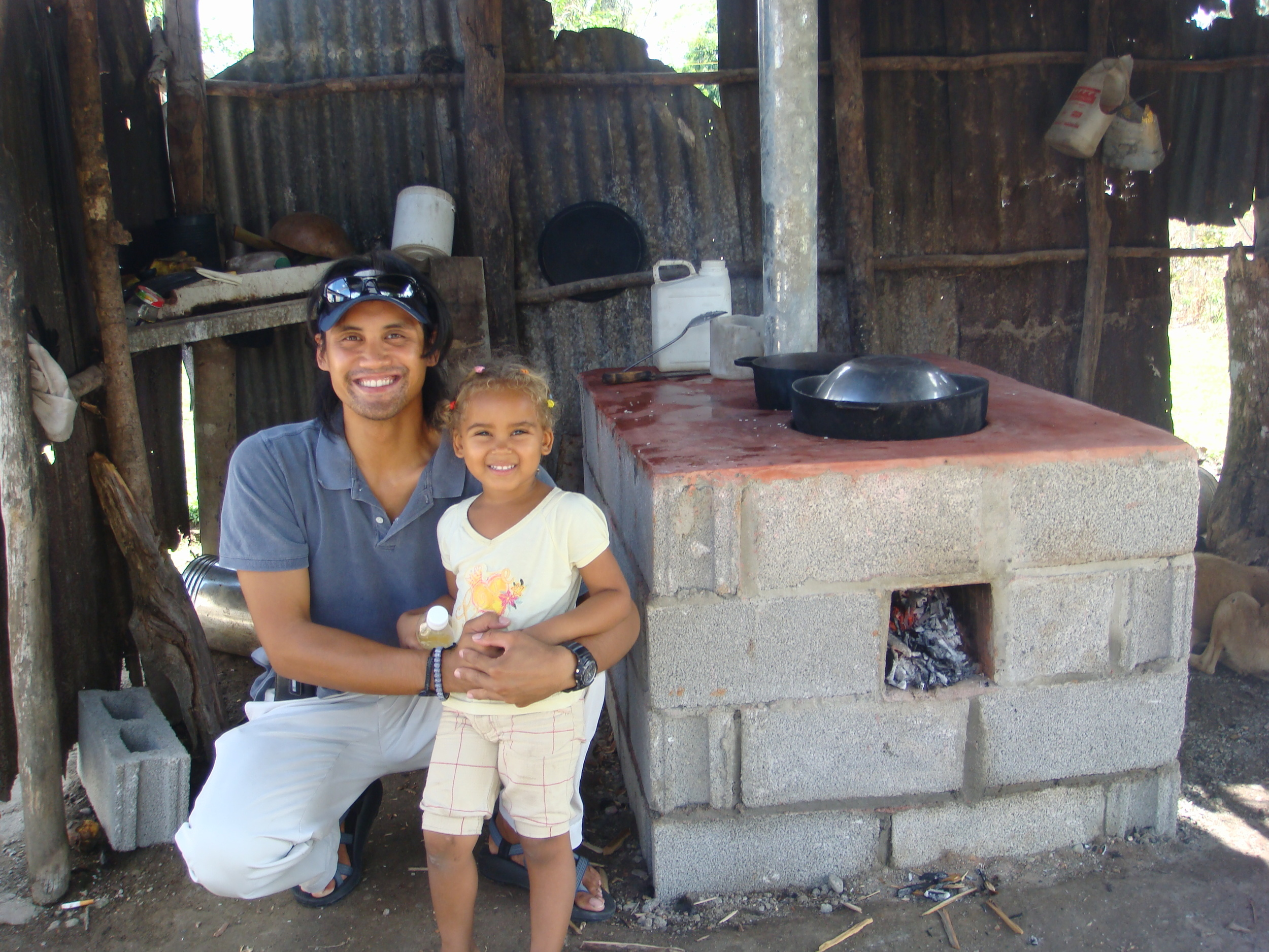 Justin with his neighbor's daughter next to a completed energy efficient stove.
