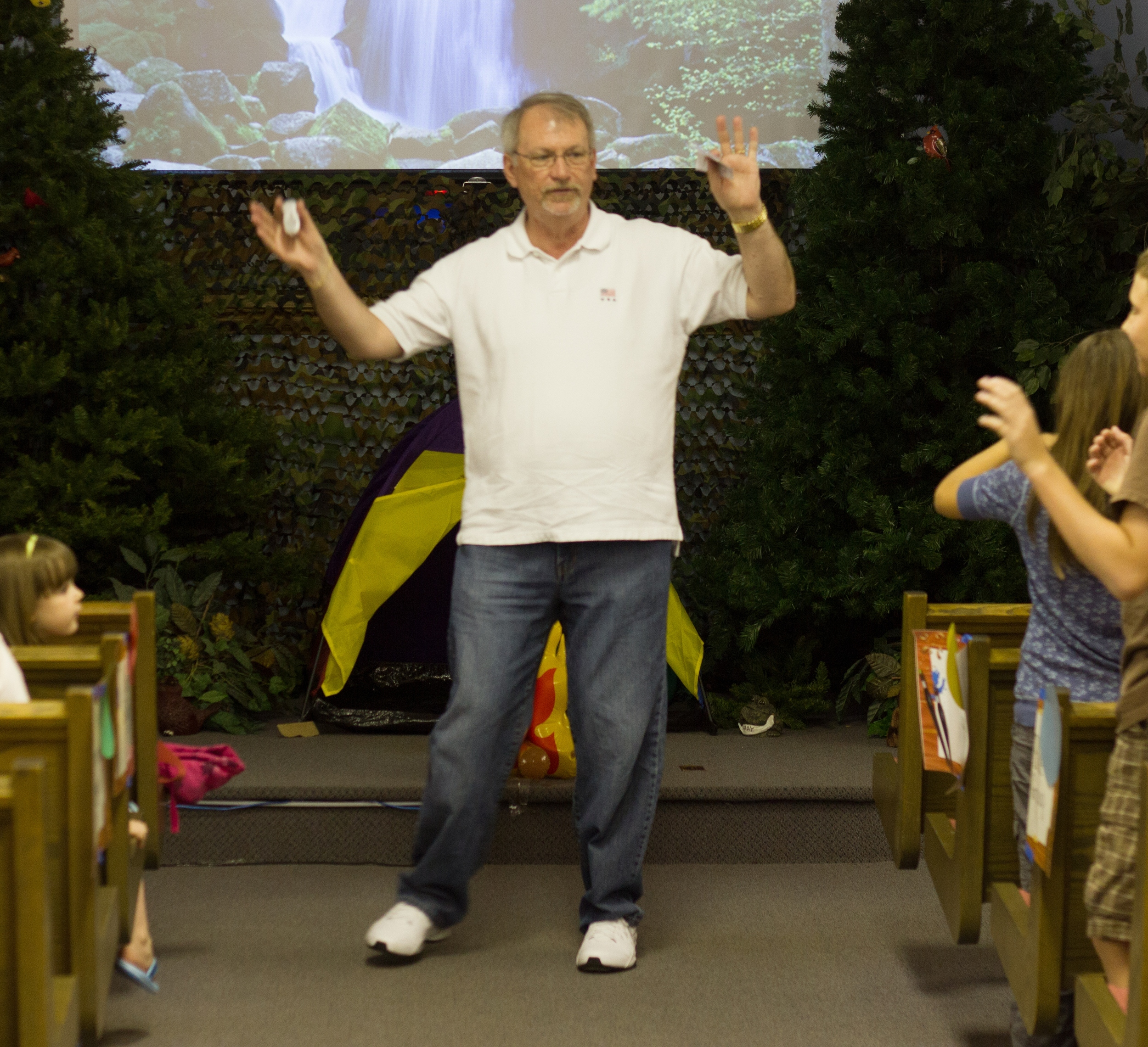 Randy Cass (Elder) in white, leading children in a song during a Vacation Bible School (VBS) event.