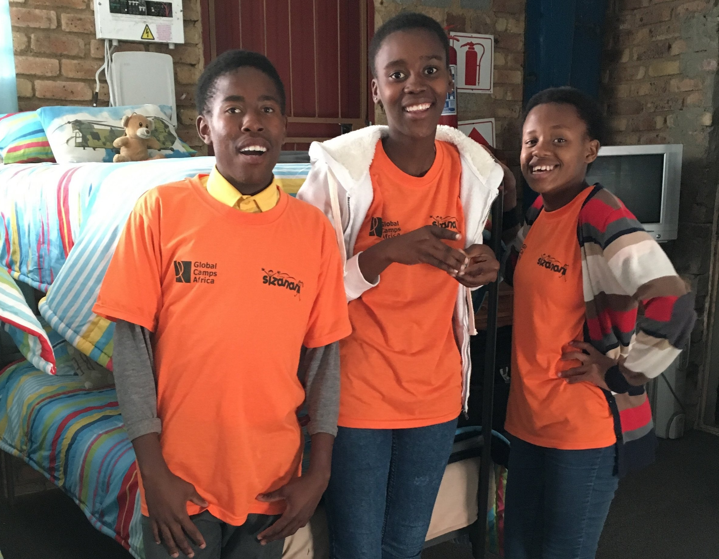 Mpho* and his fellow campers standing beside the bed where he slept at Banakekeleni Orphanage as a young child.