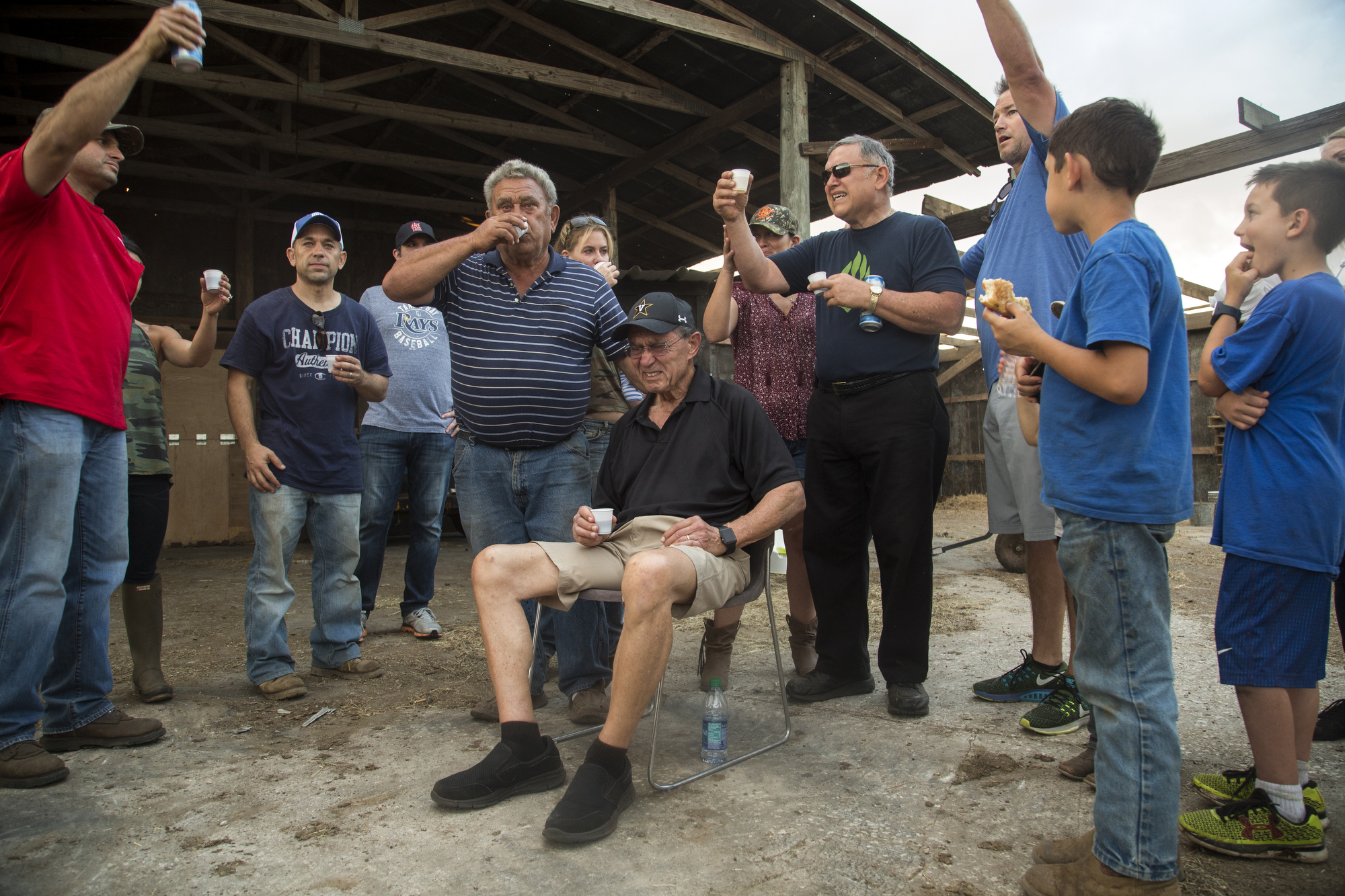 Sammy Busciglio (left of center), his two brothers and extended family toast to Tower Dairy and the Busciglio family with wine and Busch beer, on March 26, 2017, the day before the cows were moved to Georgia. Sammy's father Joe Busciglio loved to drink Busch beer. Although Jeff and Sammy own the dairy, the property was owned by a larger group of family who were ready to sell.