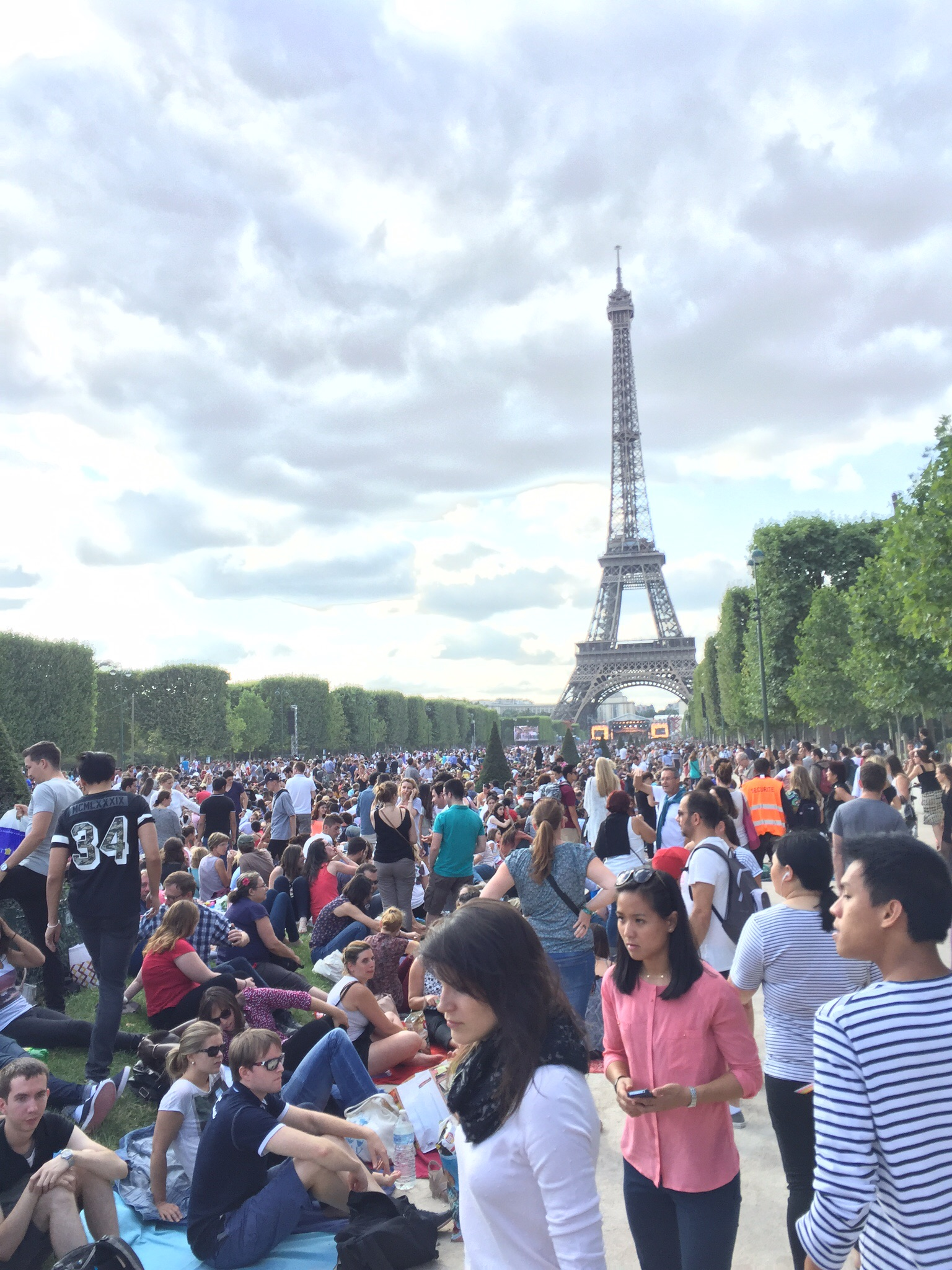 The crowd on the Champ de Mars on Bastille Day 2015. The distant concert stage is lit up under the Eiffel Tower.