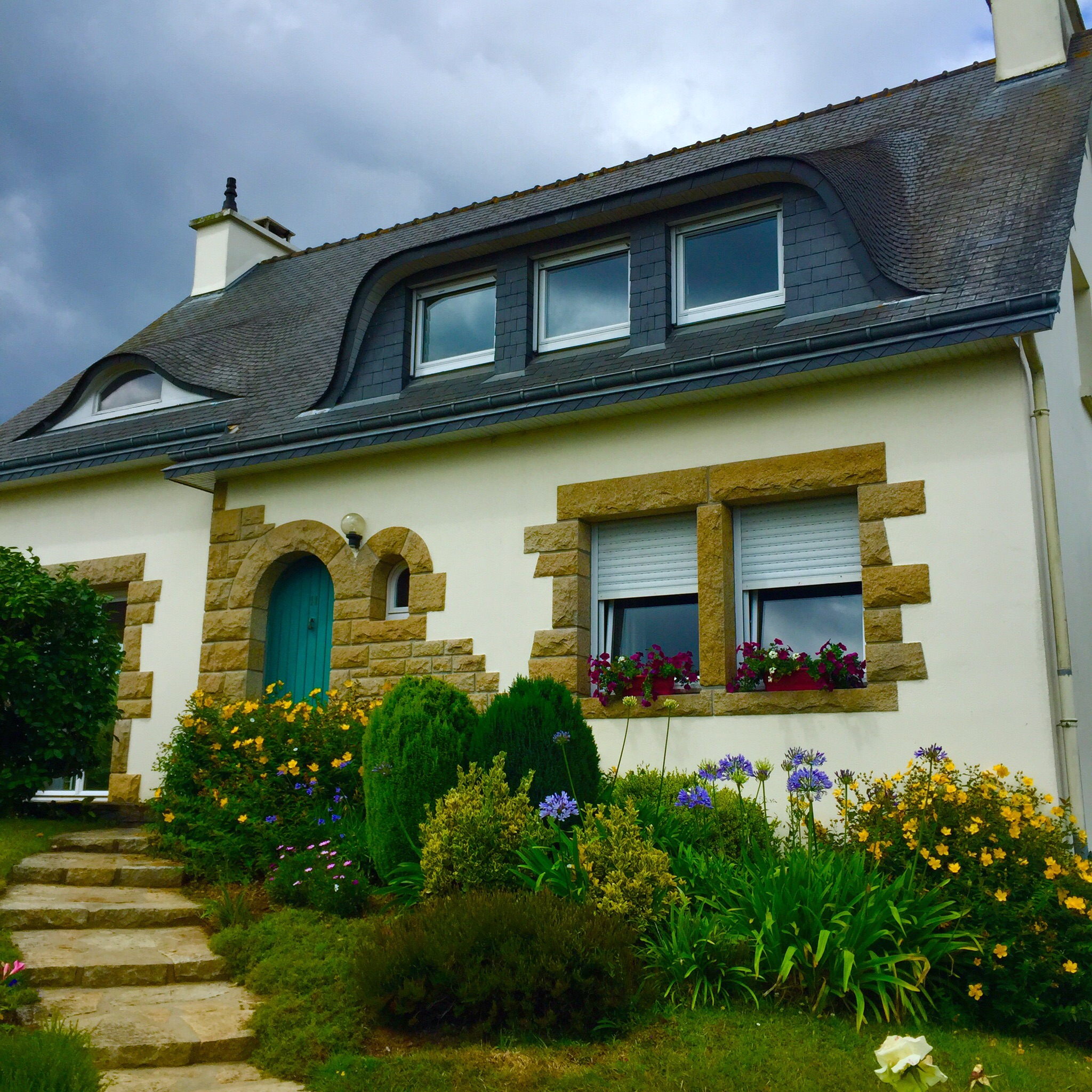 A typical Breton house in Brittany--rounded door, white walls, stone accents, and such charm