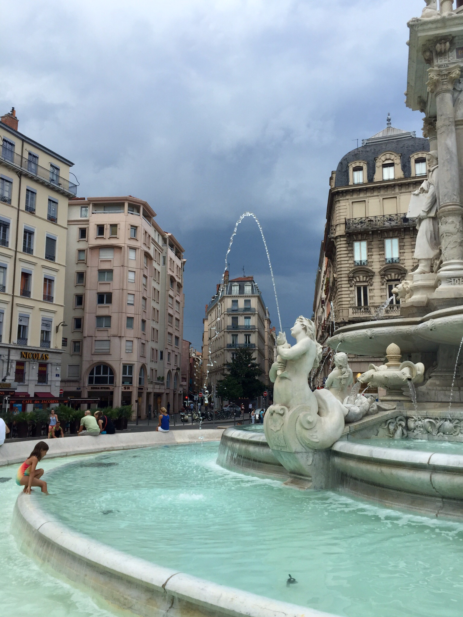 My daughter stepping into the fountain at Place des Jacobins, Lyon, just before the storm arrived