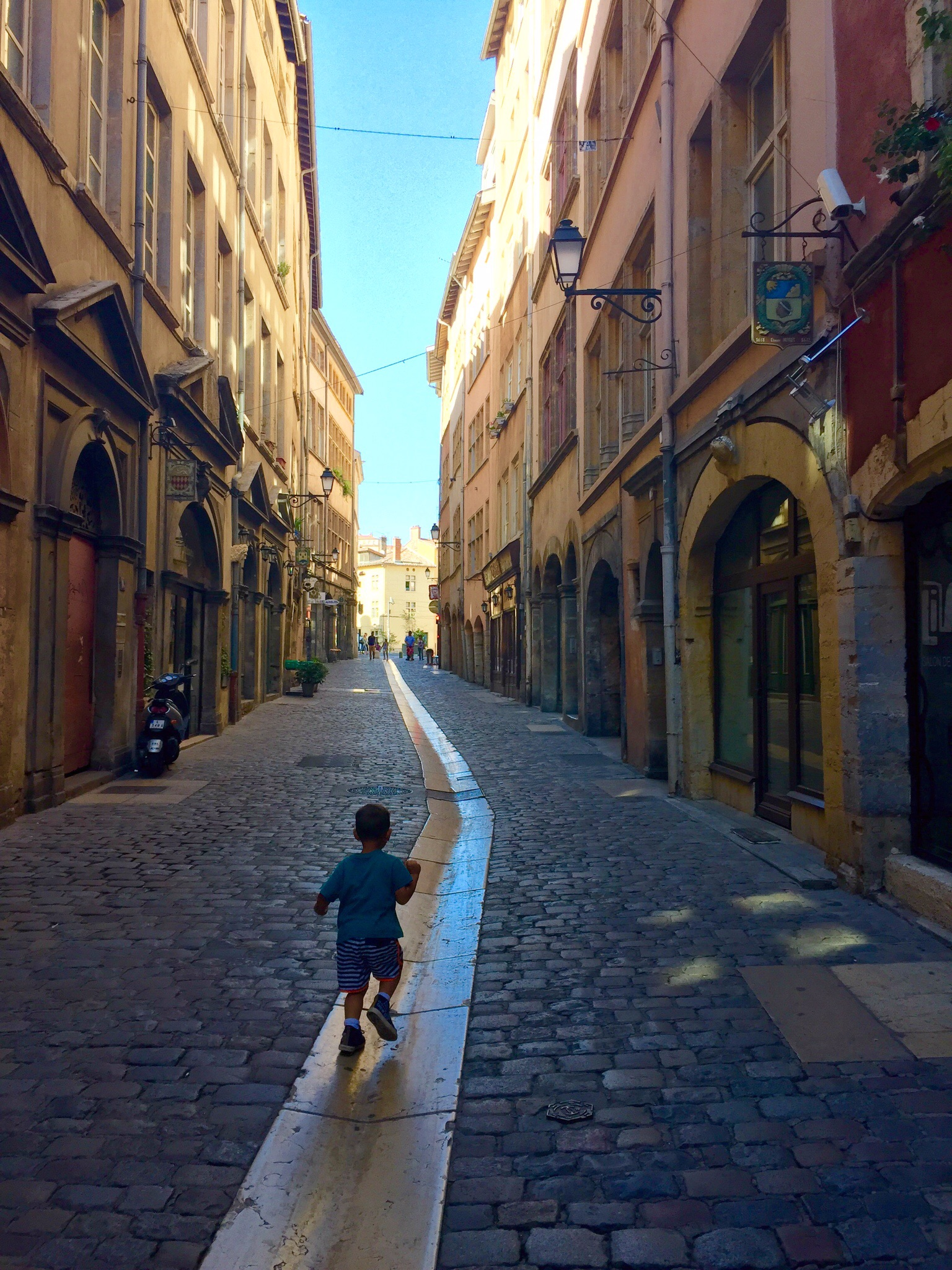 My son running down a street in Vieux Lyon