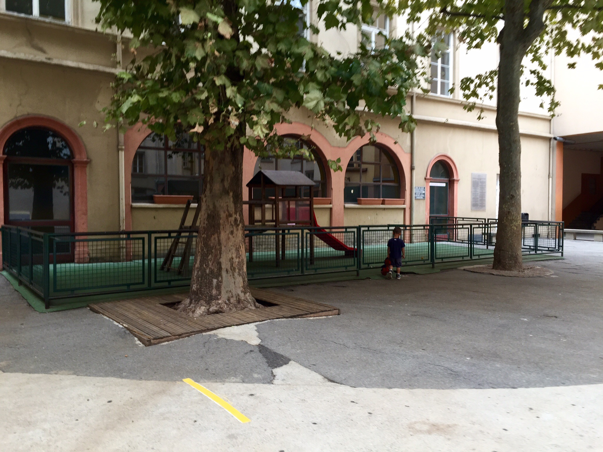A French school courtyard--mostly   concrete, with a small play structure for the preschoolers