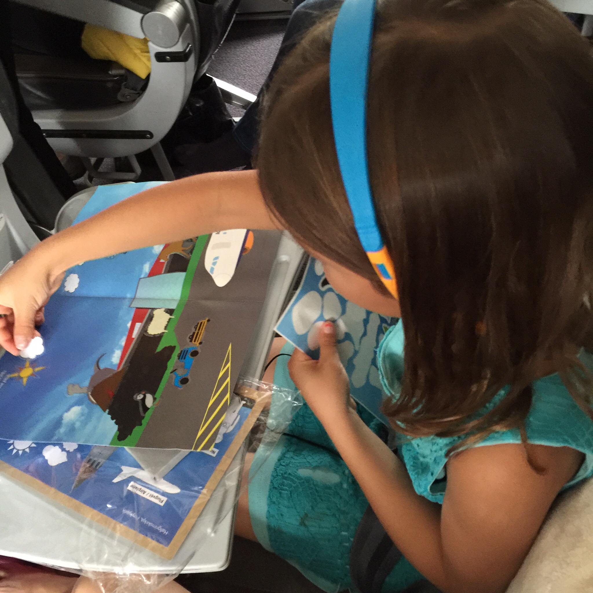 My daughter placing stickers from Iceland Air's activity pack