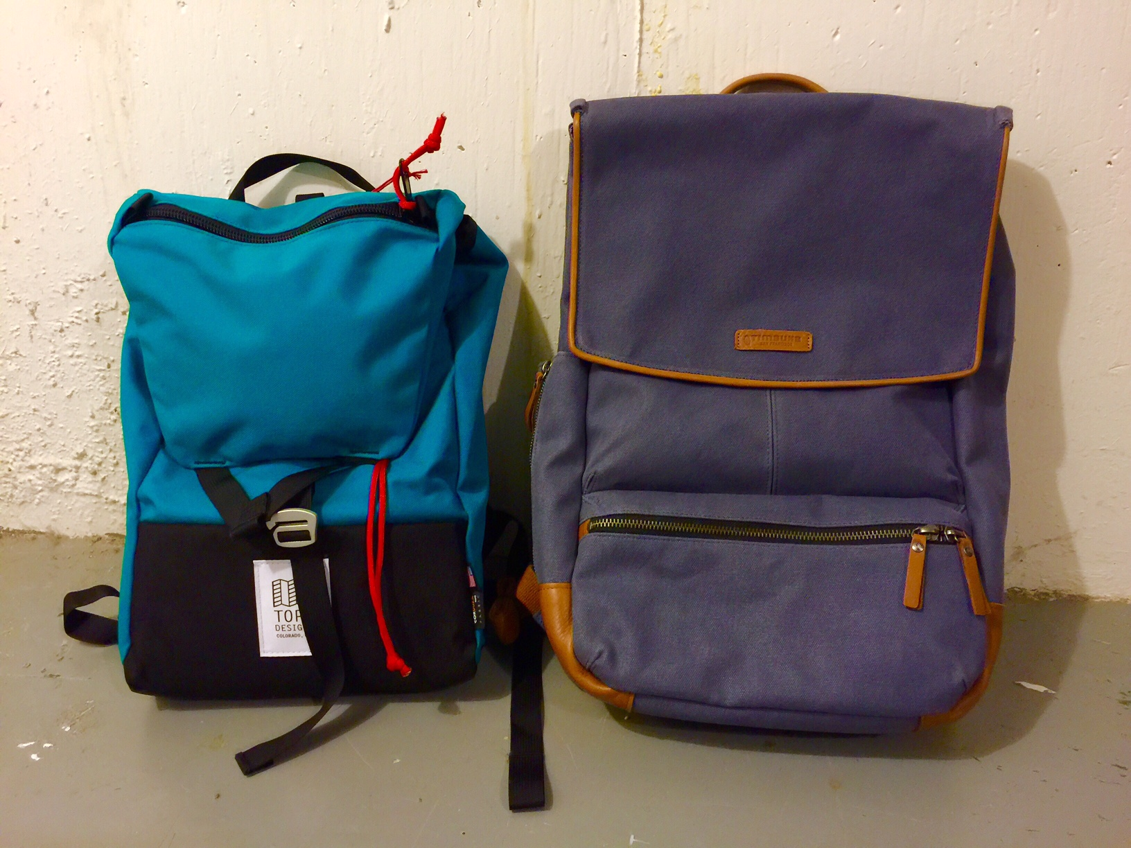 Left: Topo Designs Y-Pack (named for its strap & closure, presumably) in turquoise. Right: Timbuk2 Walker, 2014 model, in midnight.  (Photo color-corrected due to cold, poor lighting.)