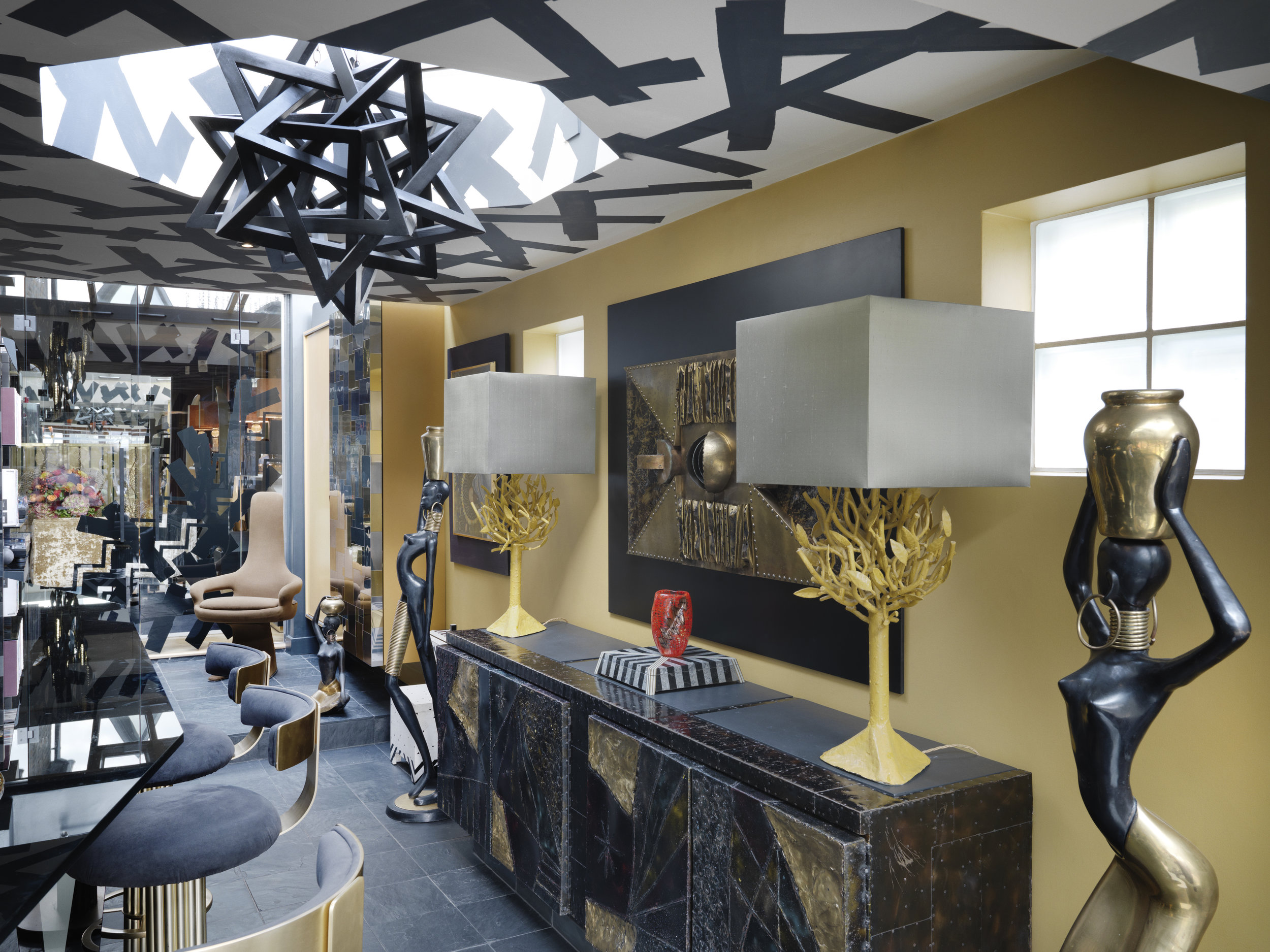 A pair of statuesque ladies very much inspired by Hagenauer designs flank a sideboard by the American Brutalist sculptor and furniture maker, Paul Evans.