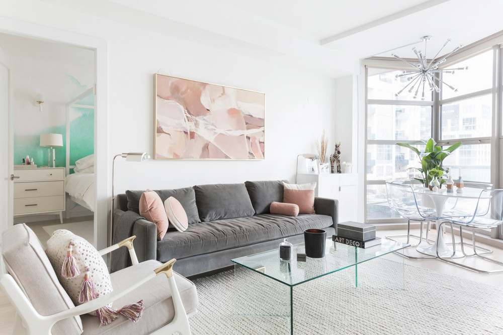 an-nyc-rental-that-looks-straight-out-of-la-grey-sofa-pink-accents-living-room-5a6fa2e2604f27084a0d4a87-w1000_h1000.jpg