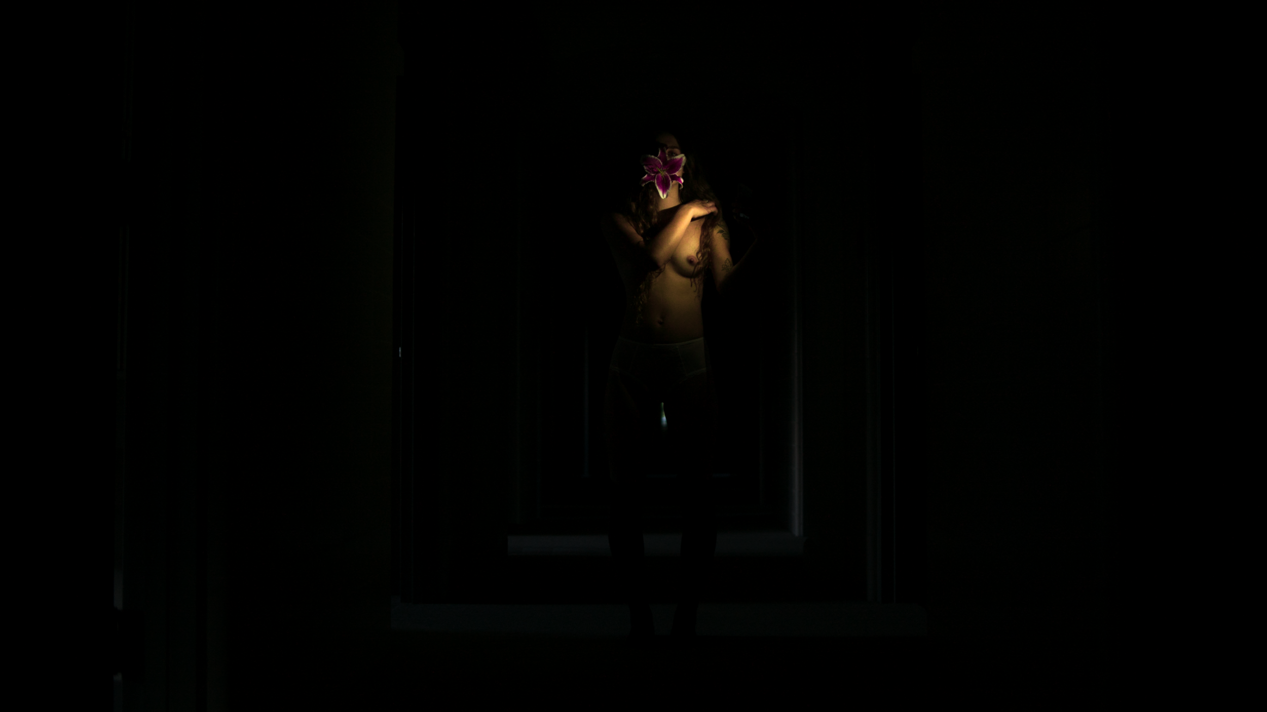 A girl stands topless in a dark hallway, an oriental lily blossom in her mouth.