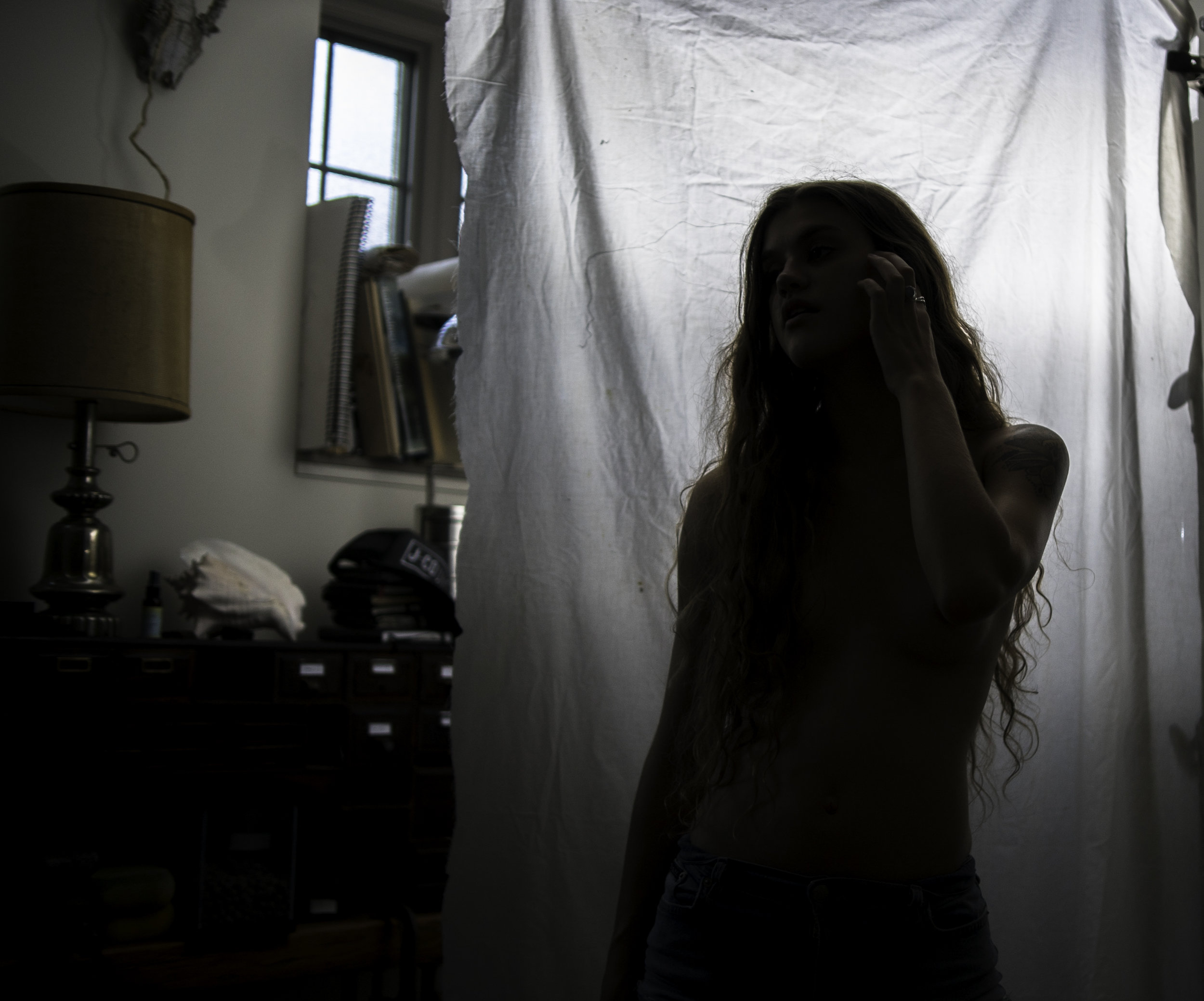 A topless girl, softly illuminated by a diffused flash.