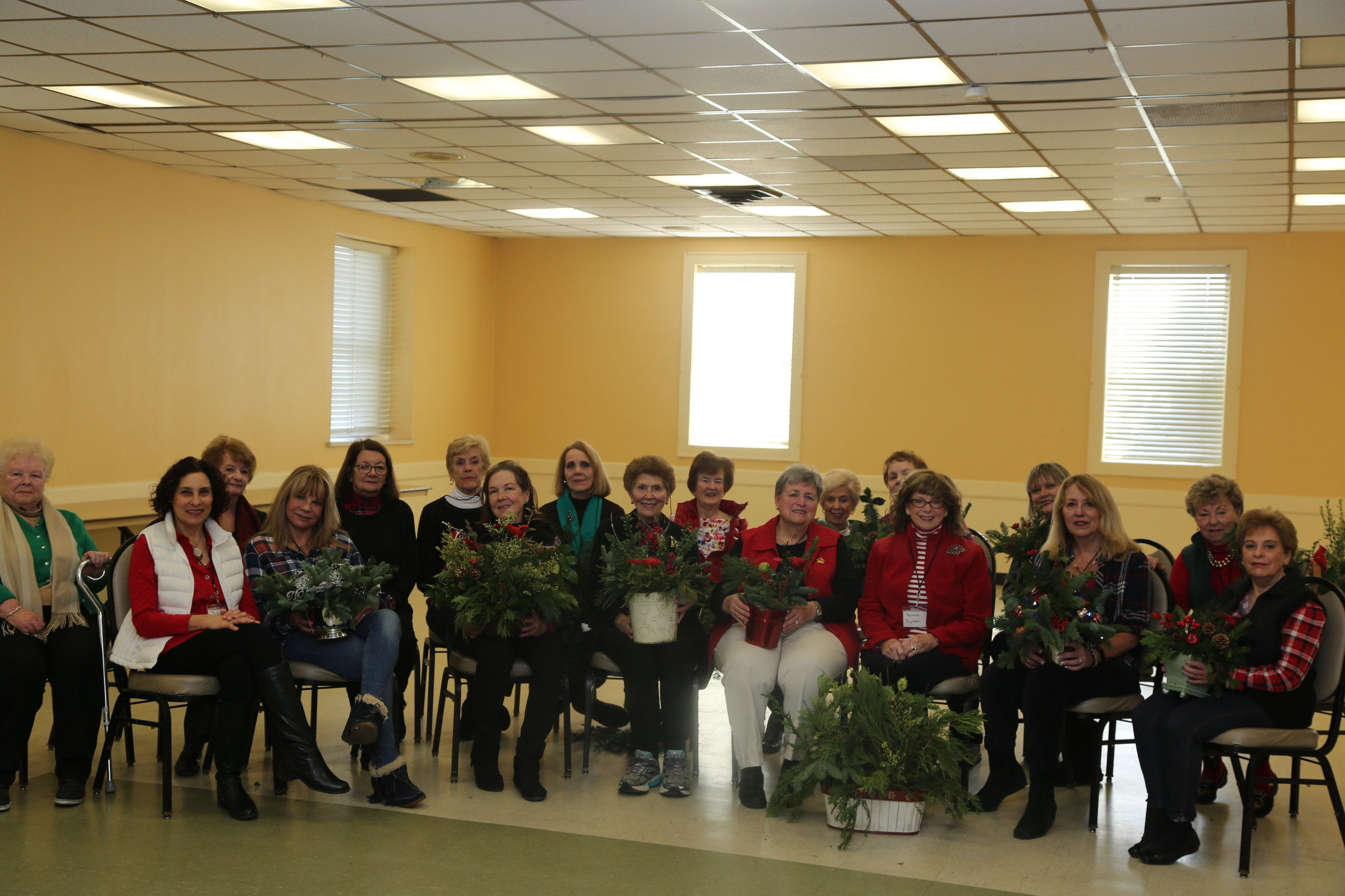 Club members at December, 2018 meeting with some of their holiday arrangements