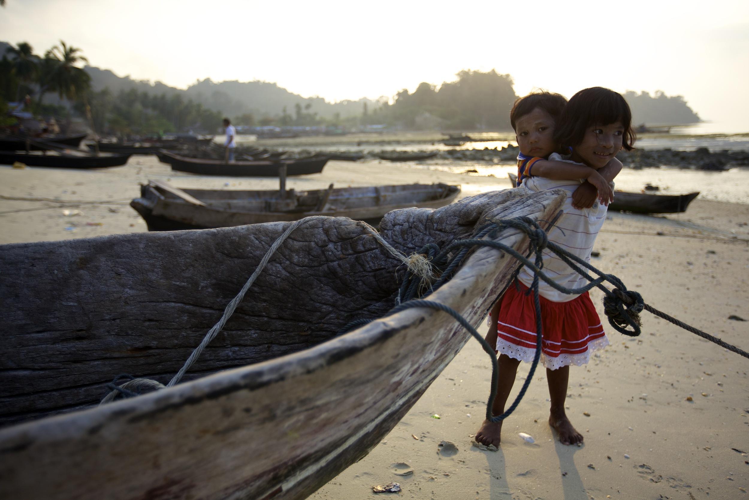 Moken children next to a dugout canoe