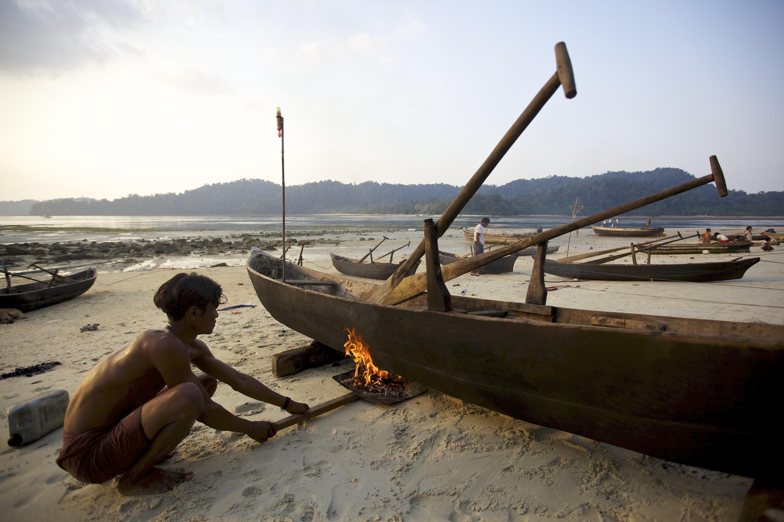 Moken man, working on his dugout canoe