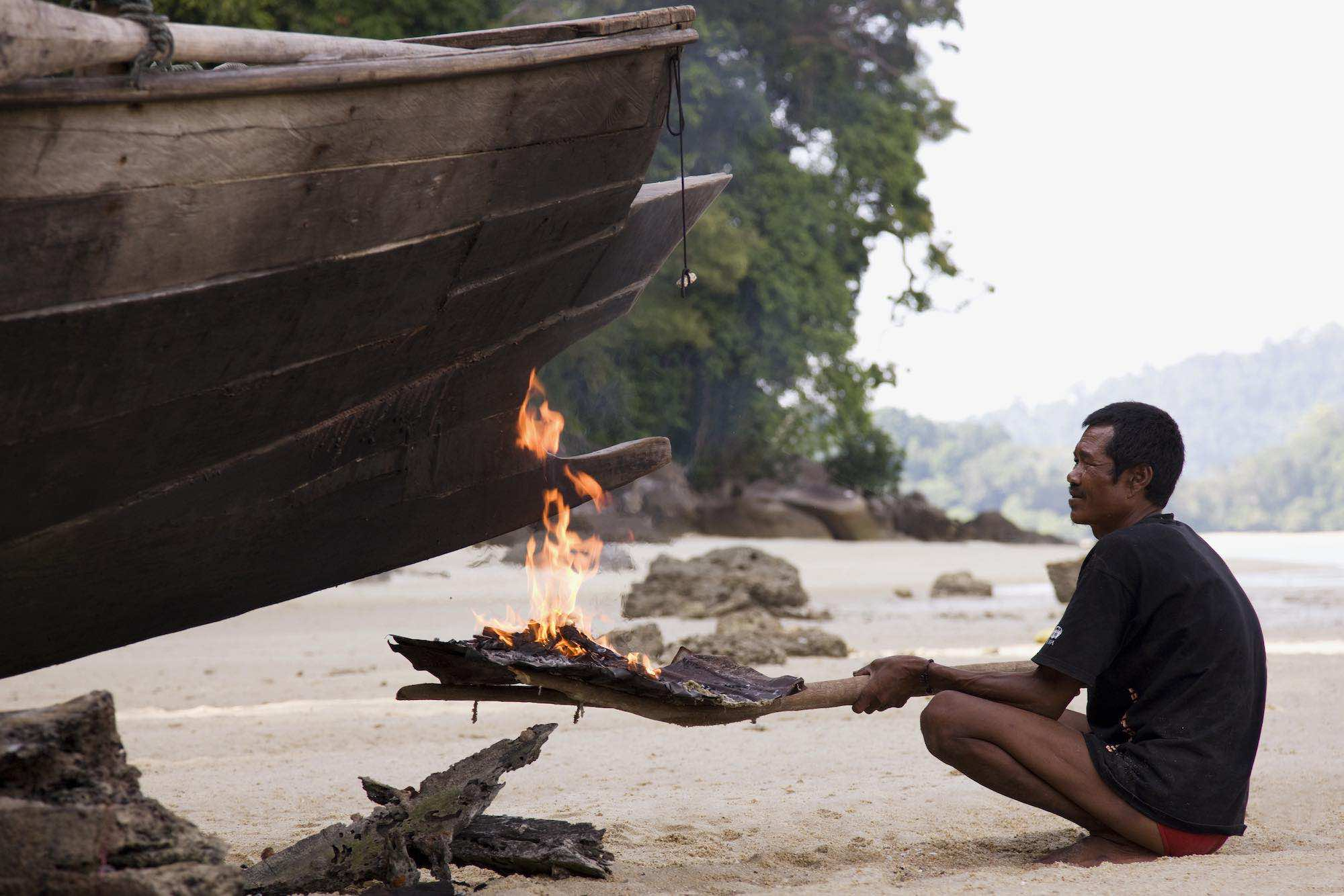 Tat burning the hull of his kabang to waterproof the boat