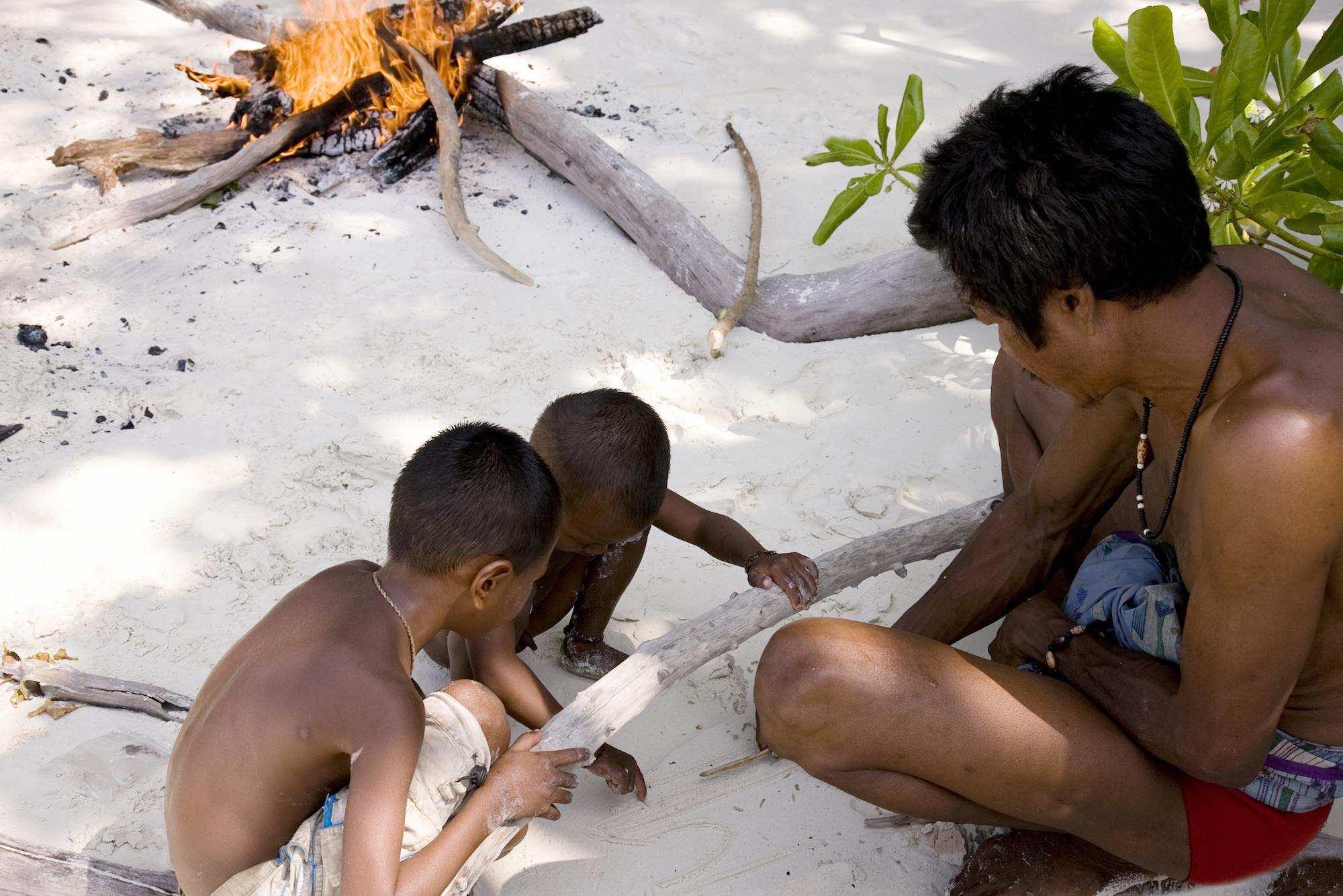 17.Tat drafting illiustrations in the sand - teaching his boys Moken life skills.jpeg
